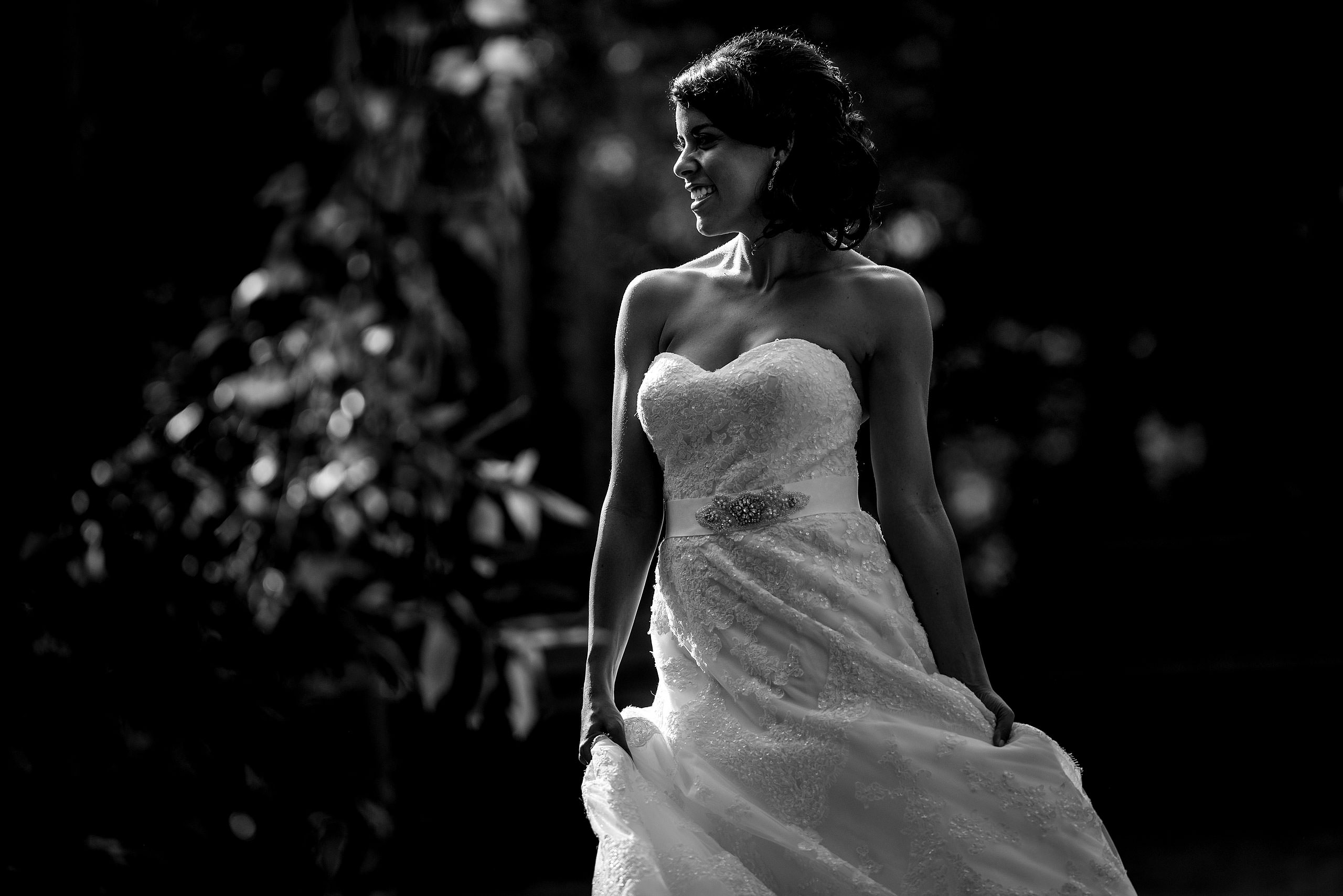 a bride swaying her dress in a park by Edmonton wedding photographer sean leblanc