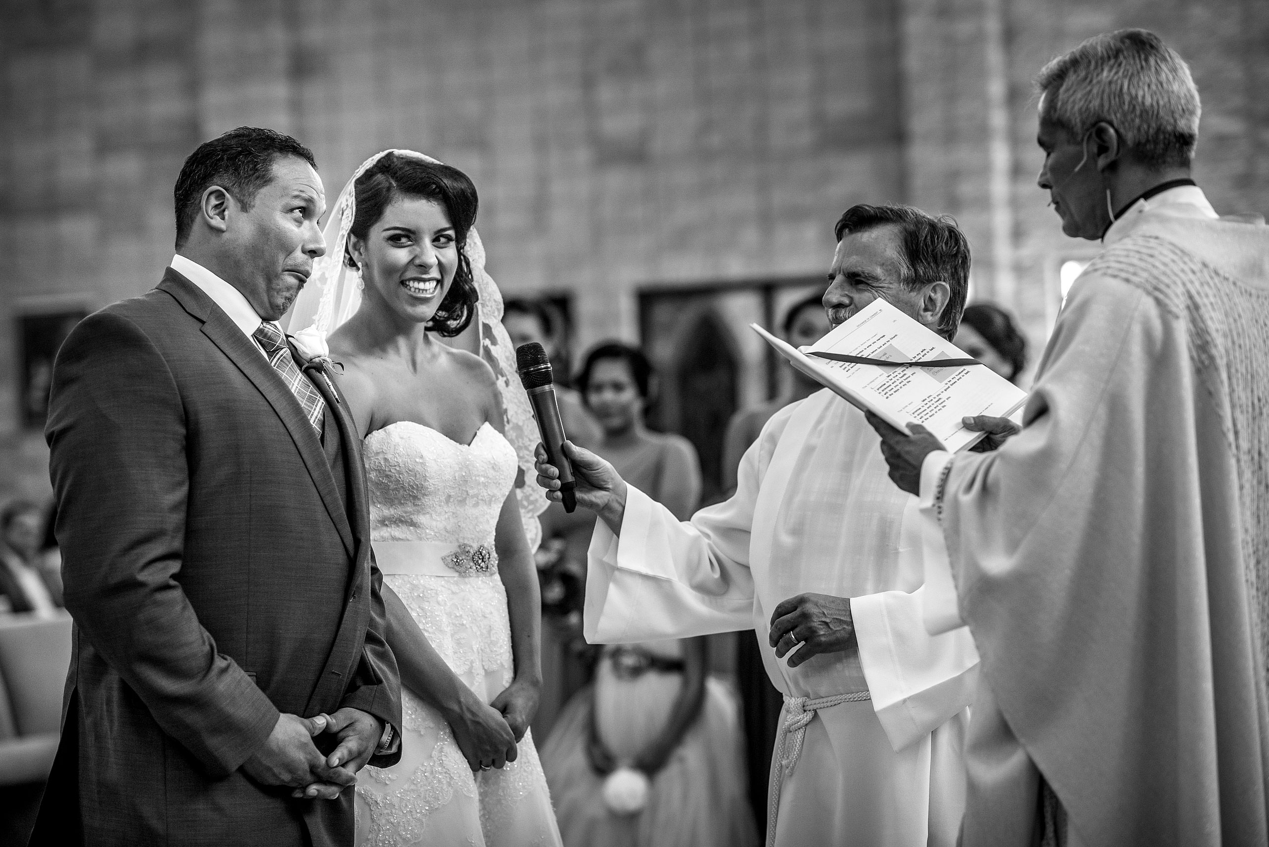 a groom making a funny face to his bride at a ceremony by Edmonton wedding photographer sean leblanc