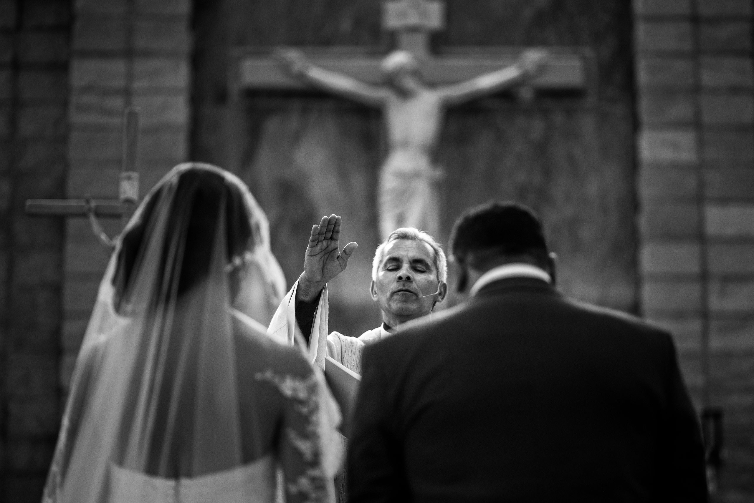 a priest praying for a bride and groom by Edmonton wedding photographer sean leblanc