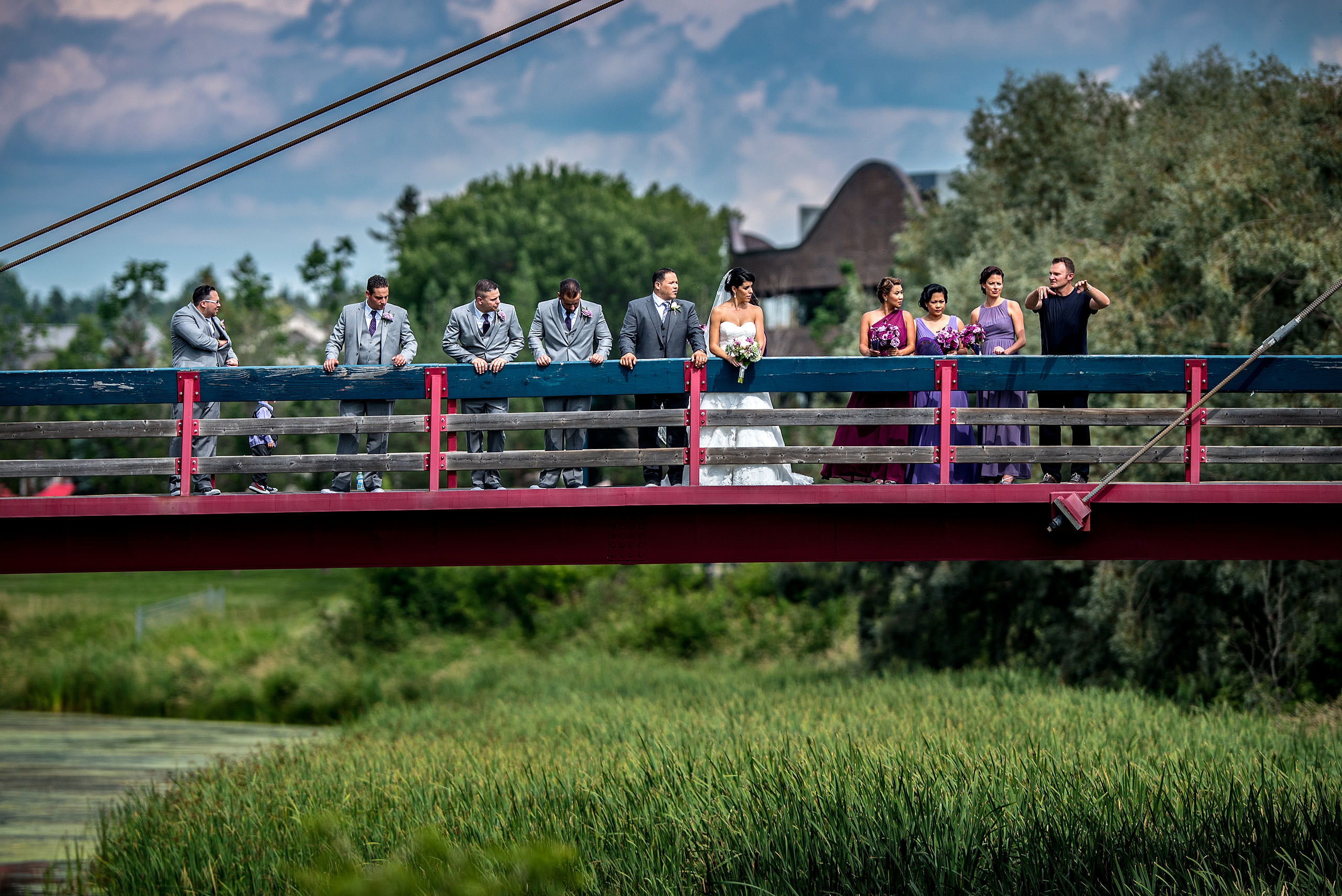 a man speaking to a bridal party on a bridge by Edmonton wedding photographer sean leblanc