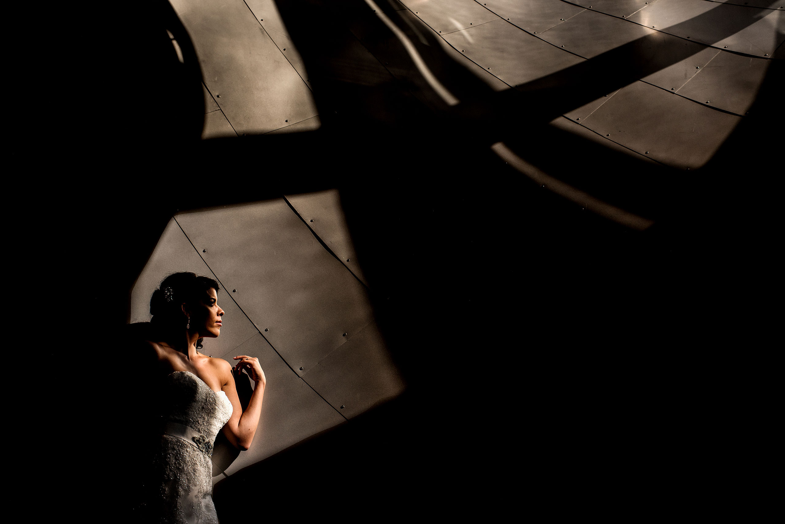 a bride leaning up against a wall at the Art Gallery of Alberta by Edmonton wedding photographer sean leblanc