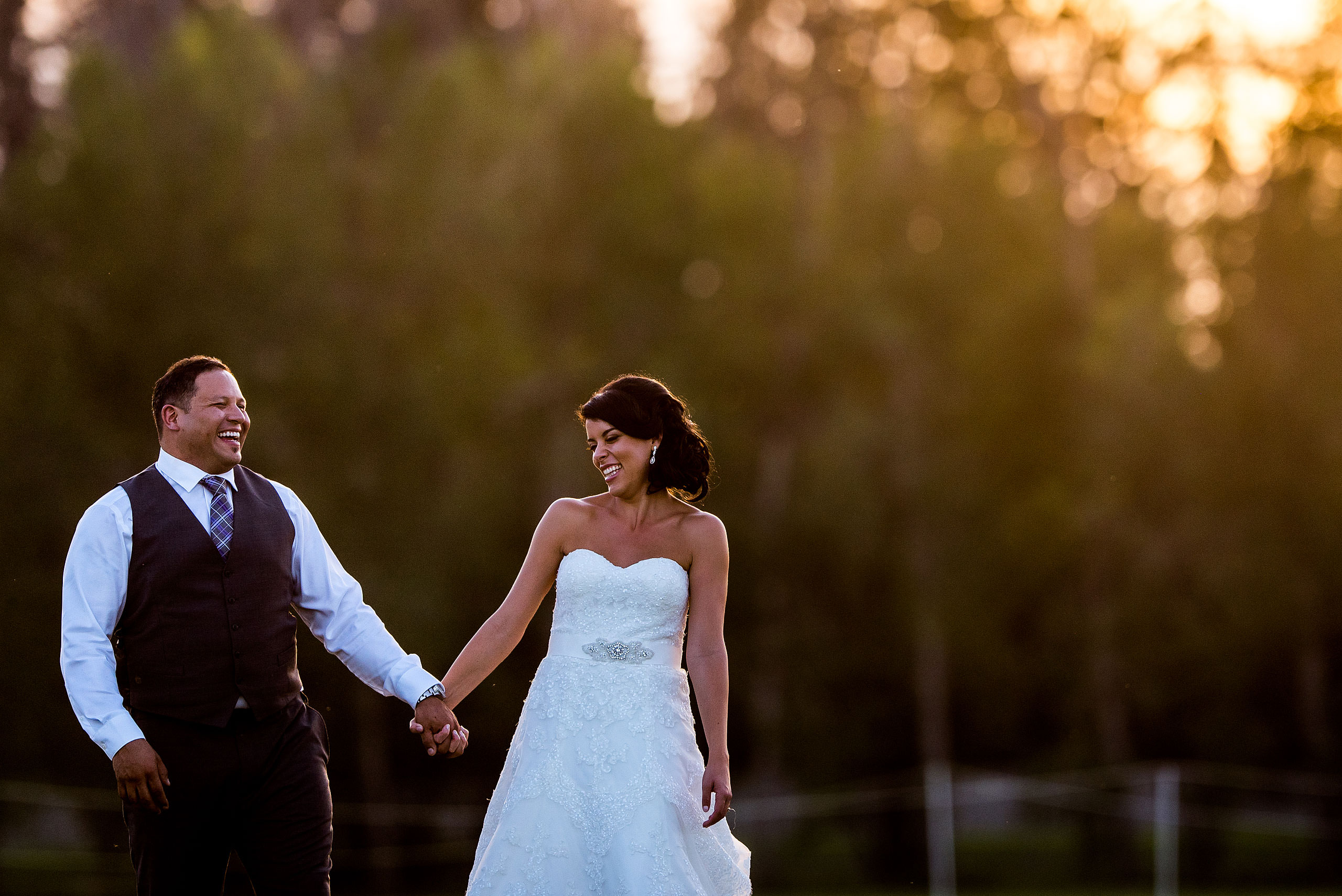 a bride and groom smiling at each other while walking in a field by Edmonton wedding photographer sean leblanc