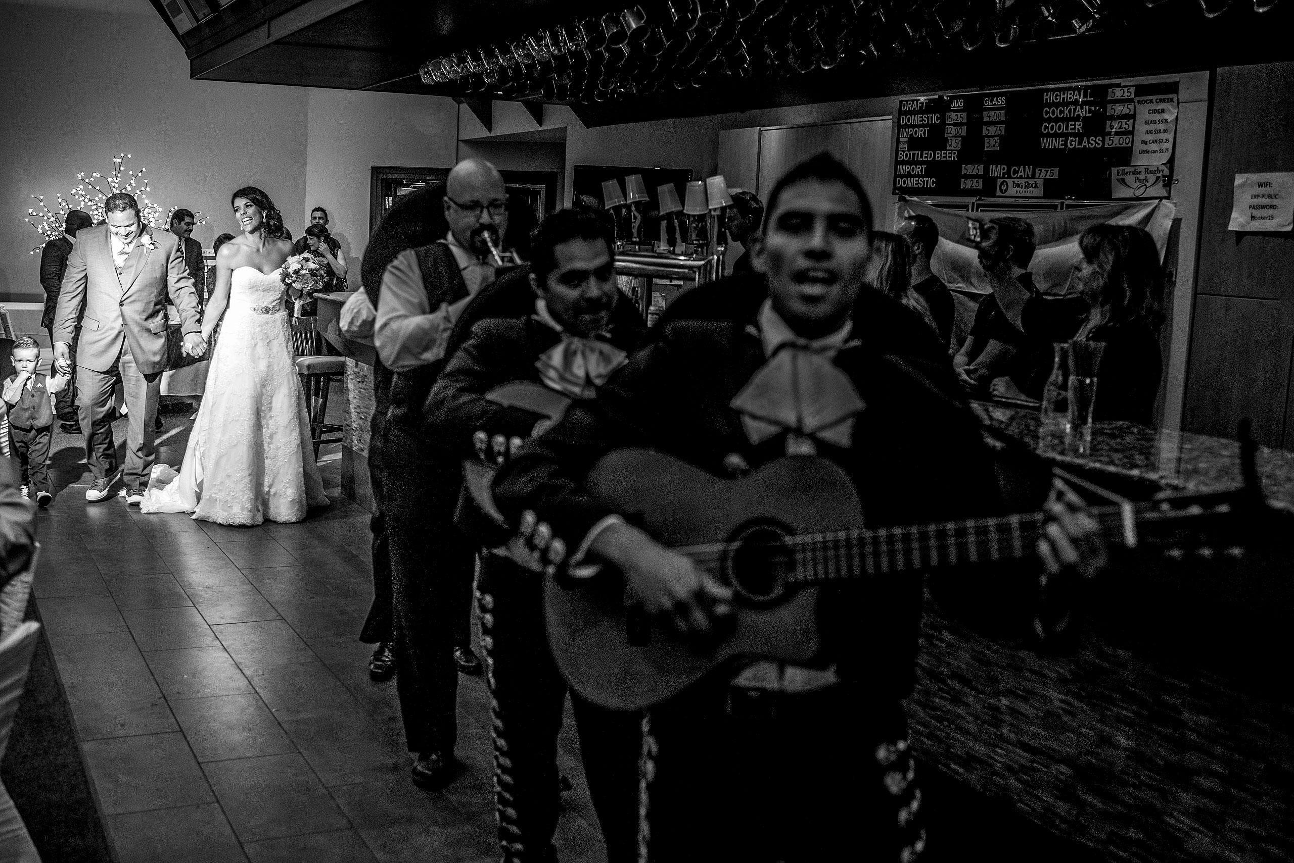 a bride and groom walking into a reception led by a mariachi band by Edmonton wedding photographer sean leblanc
