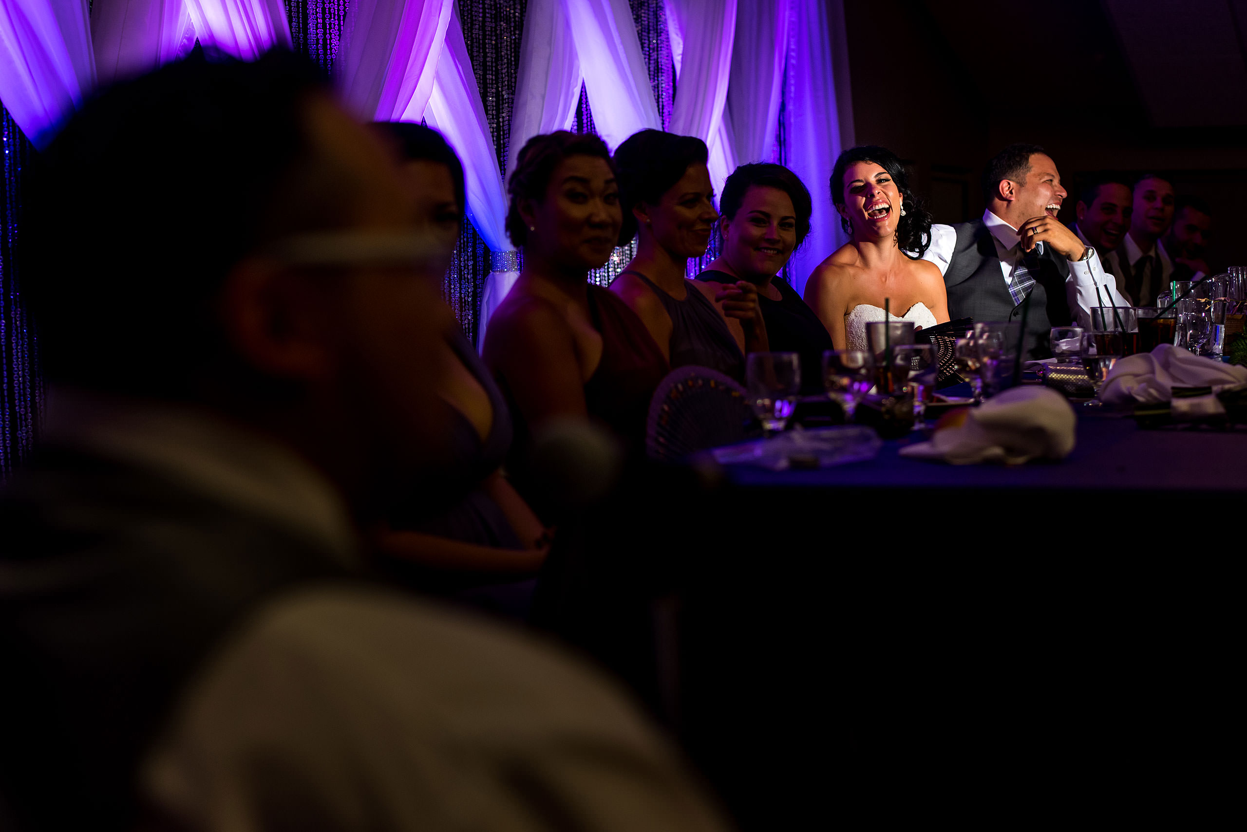 a bride and groom laughing at a speech by Edmonton wedding photographer sean leblanc