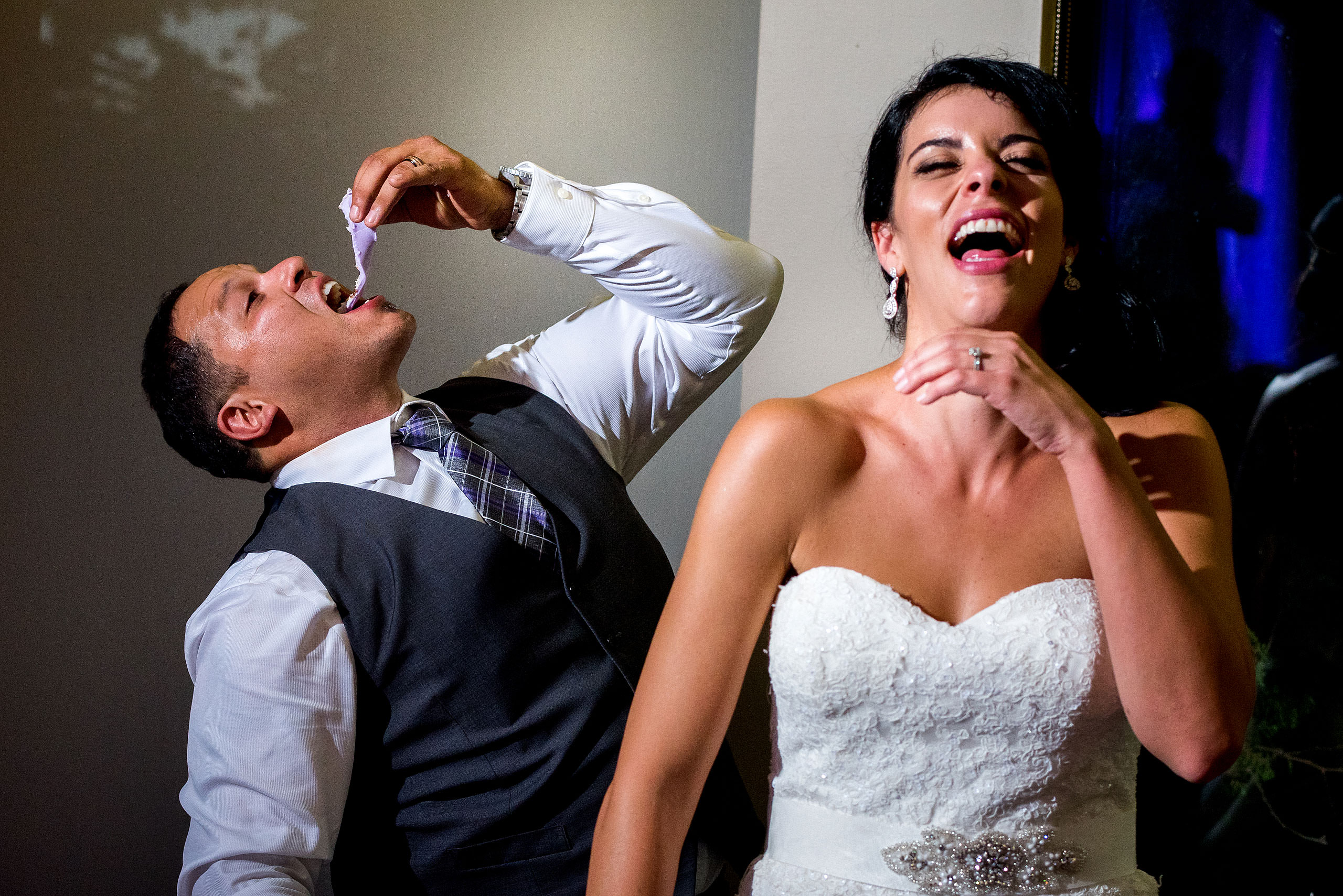 a groom eating a wedding cake with his bride laughing by Edmonton wedding photographer sean leblanc