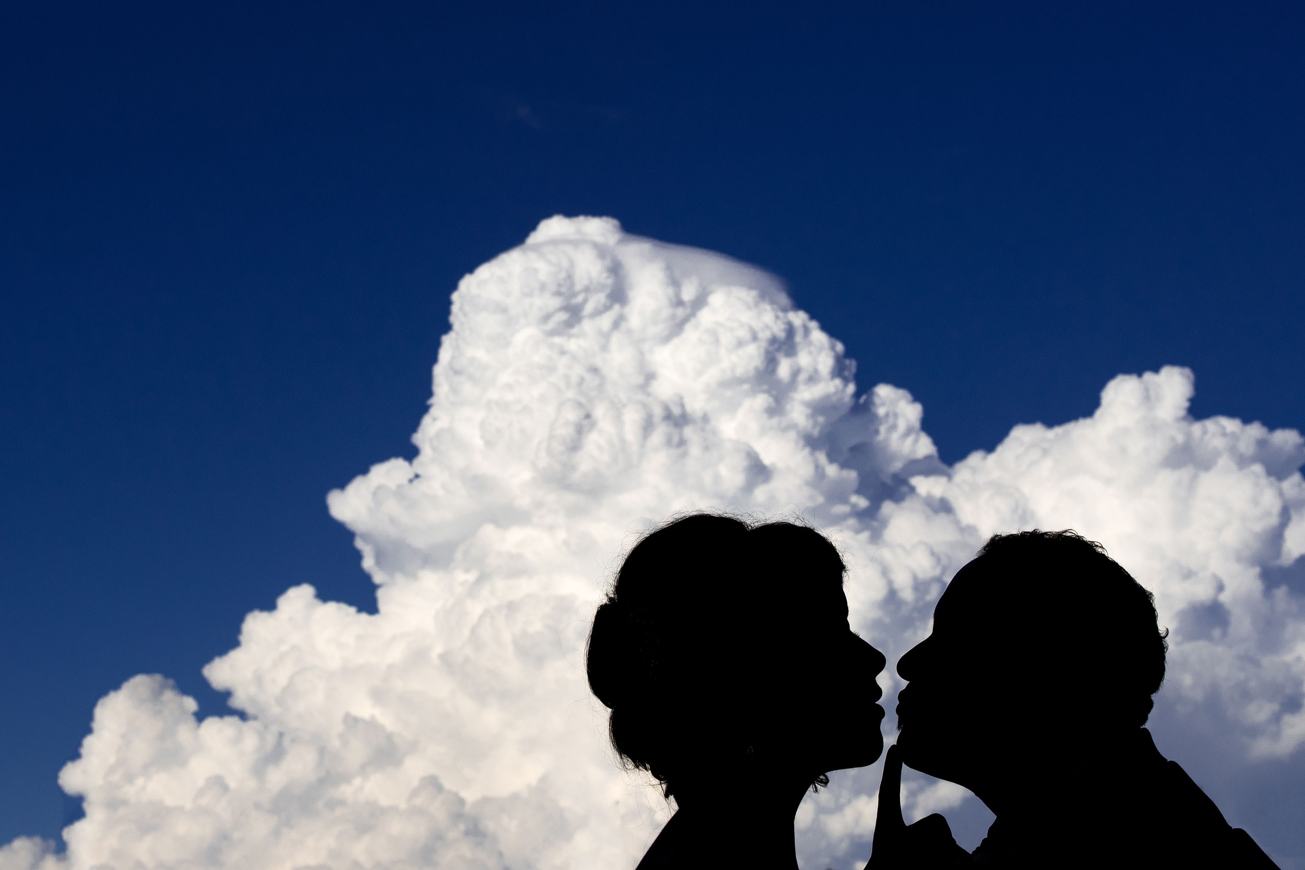 a silhouette of a bride and groom in front of a cloud by Edmonton wedding photographer sean leblanc