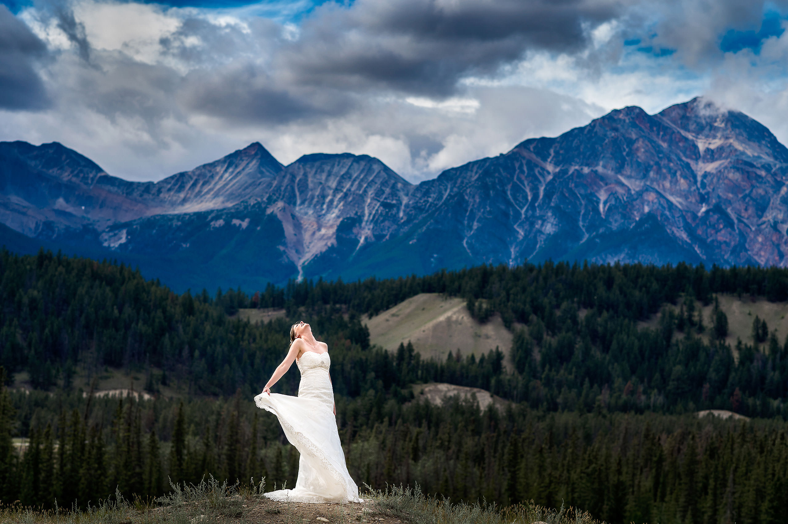 bride posing in front of a mountain by jasper wedding photographer