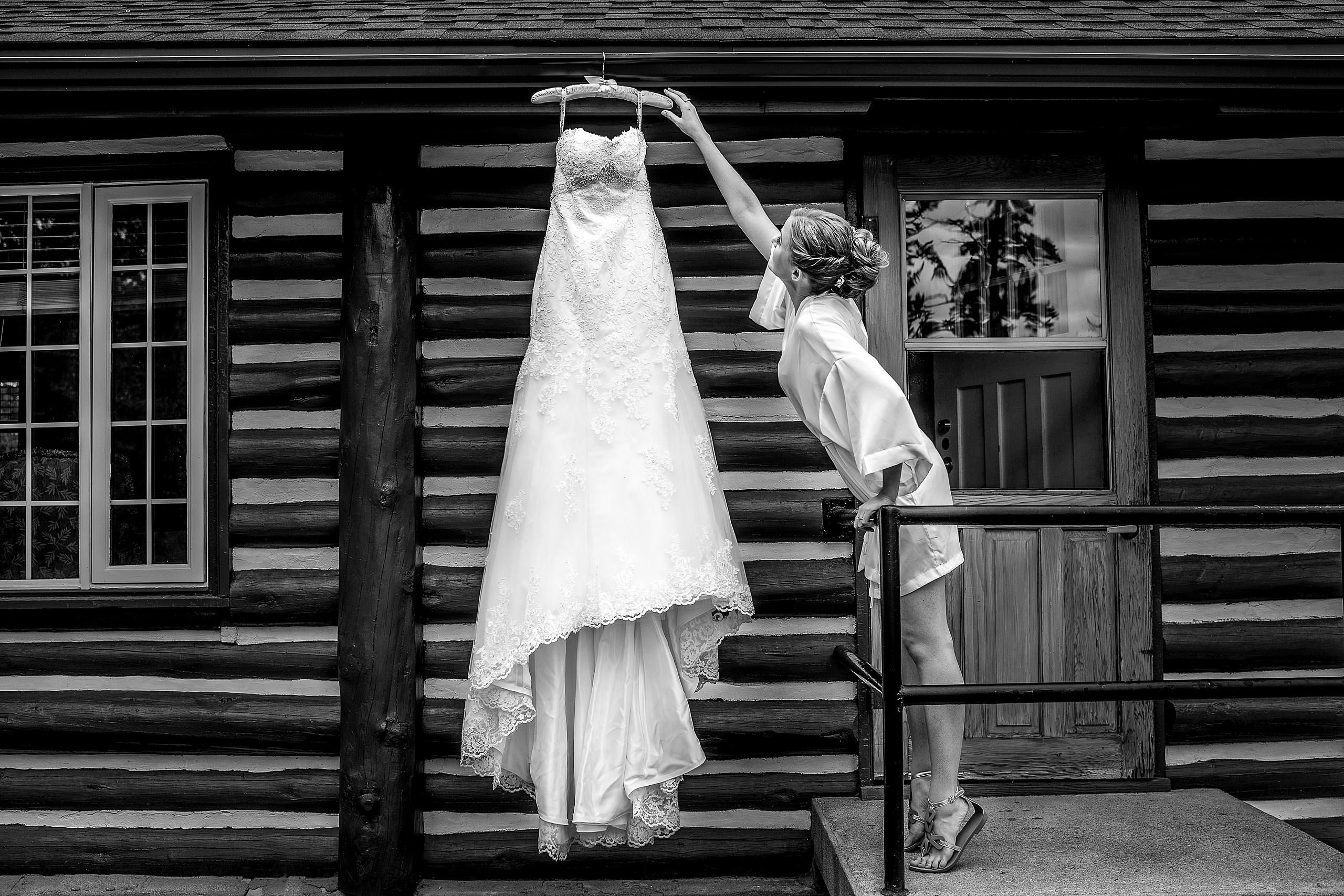 bride reaching for her dress outside of a log cabin by jasper wedding photographer