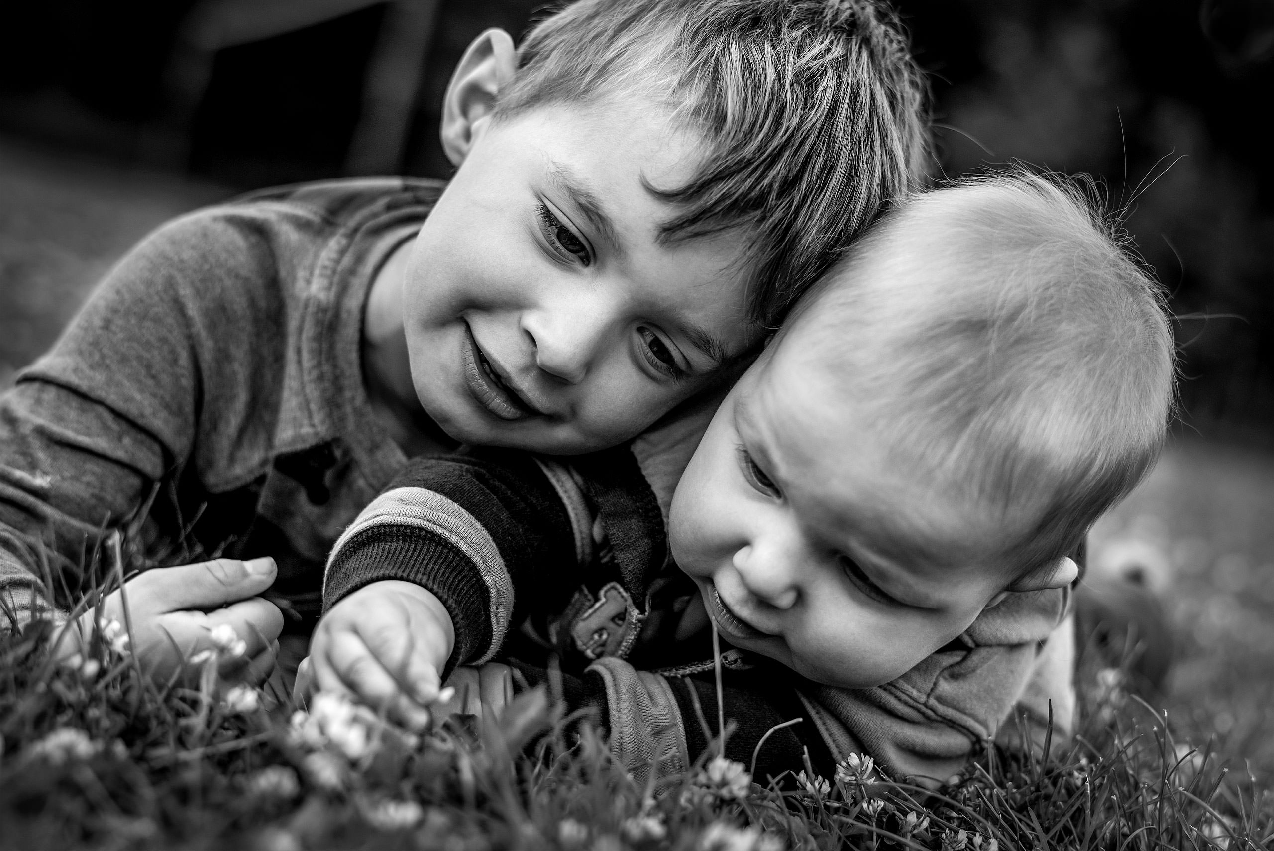 two young boys lying down in the grass playing with a flower