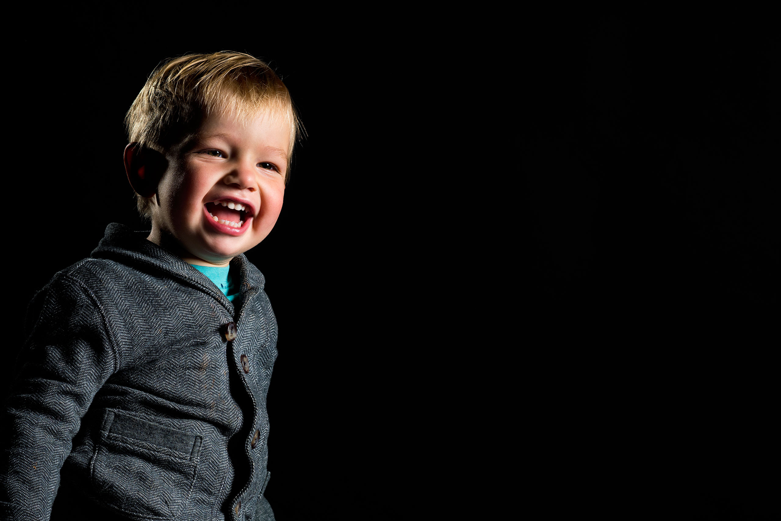Young boy dressed in nice clothes against a black backdrop smiling by top family portrait photographer sean leblanc
