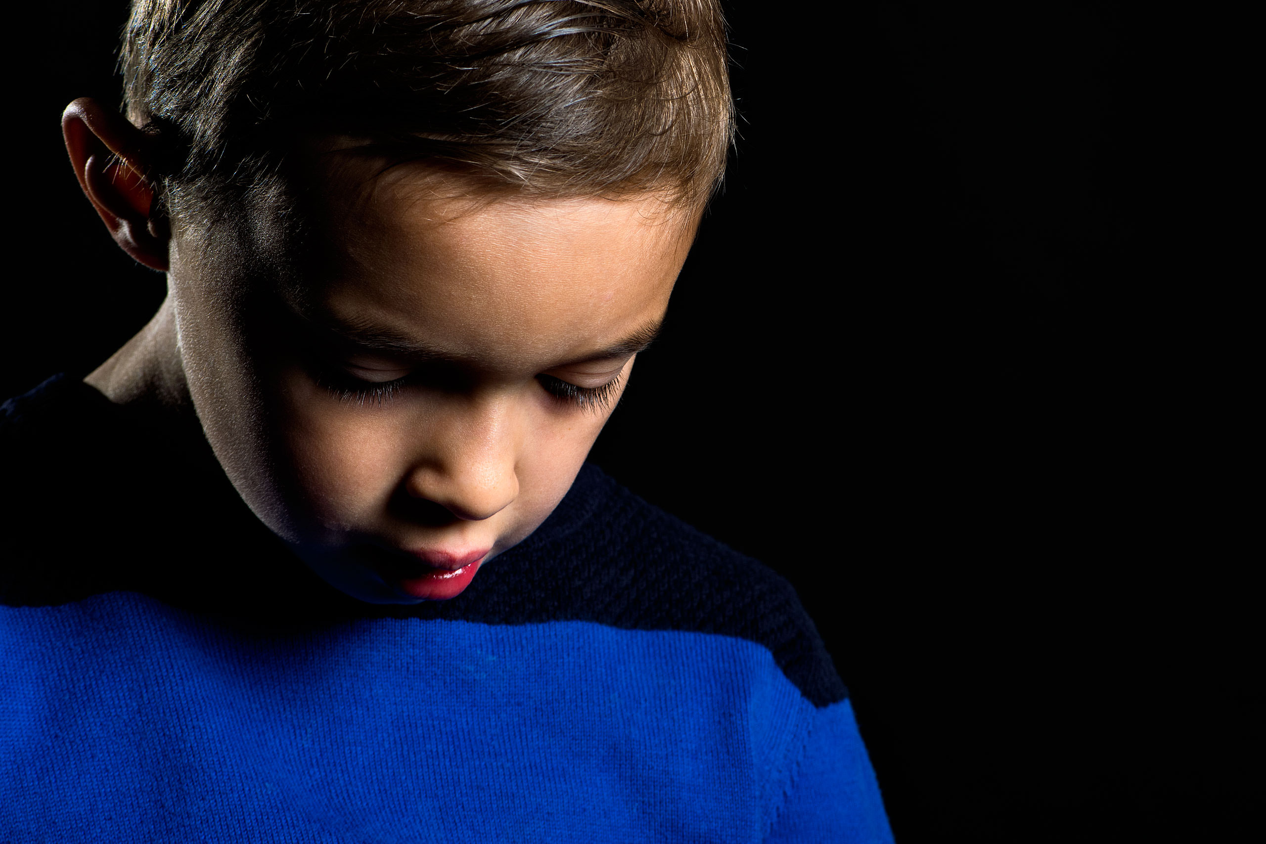 young boy looking towards the floor wearing a blue sweater on a black background by top family portrait photographer sean leblanc