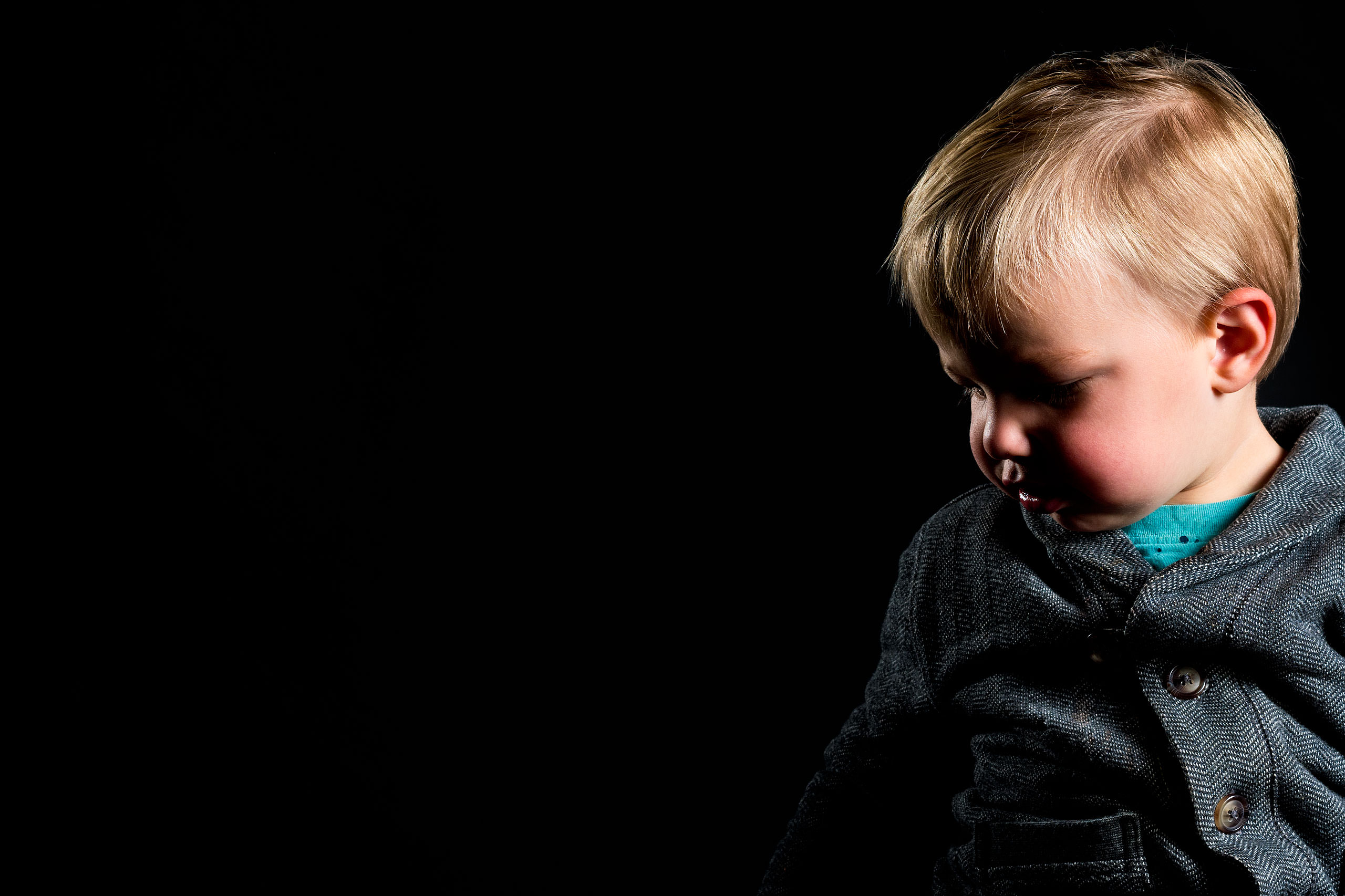a young boy looking down and wearing a grey sweater for a calgary portrait studio session by sean leblanc