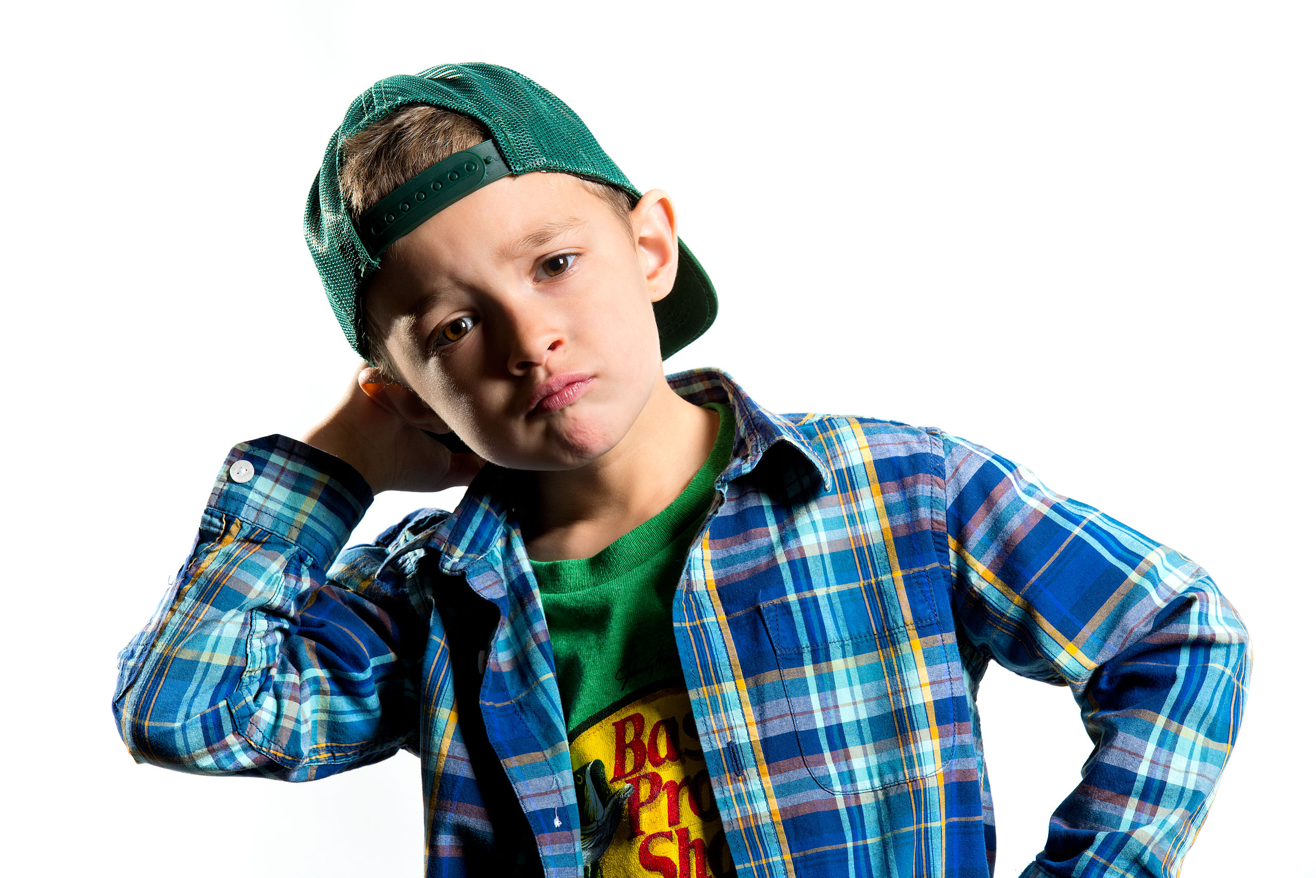 a young boy wearing a backwards green hat with his elbows sticking out for a calgary portrait studio session by sean leblanc