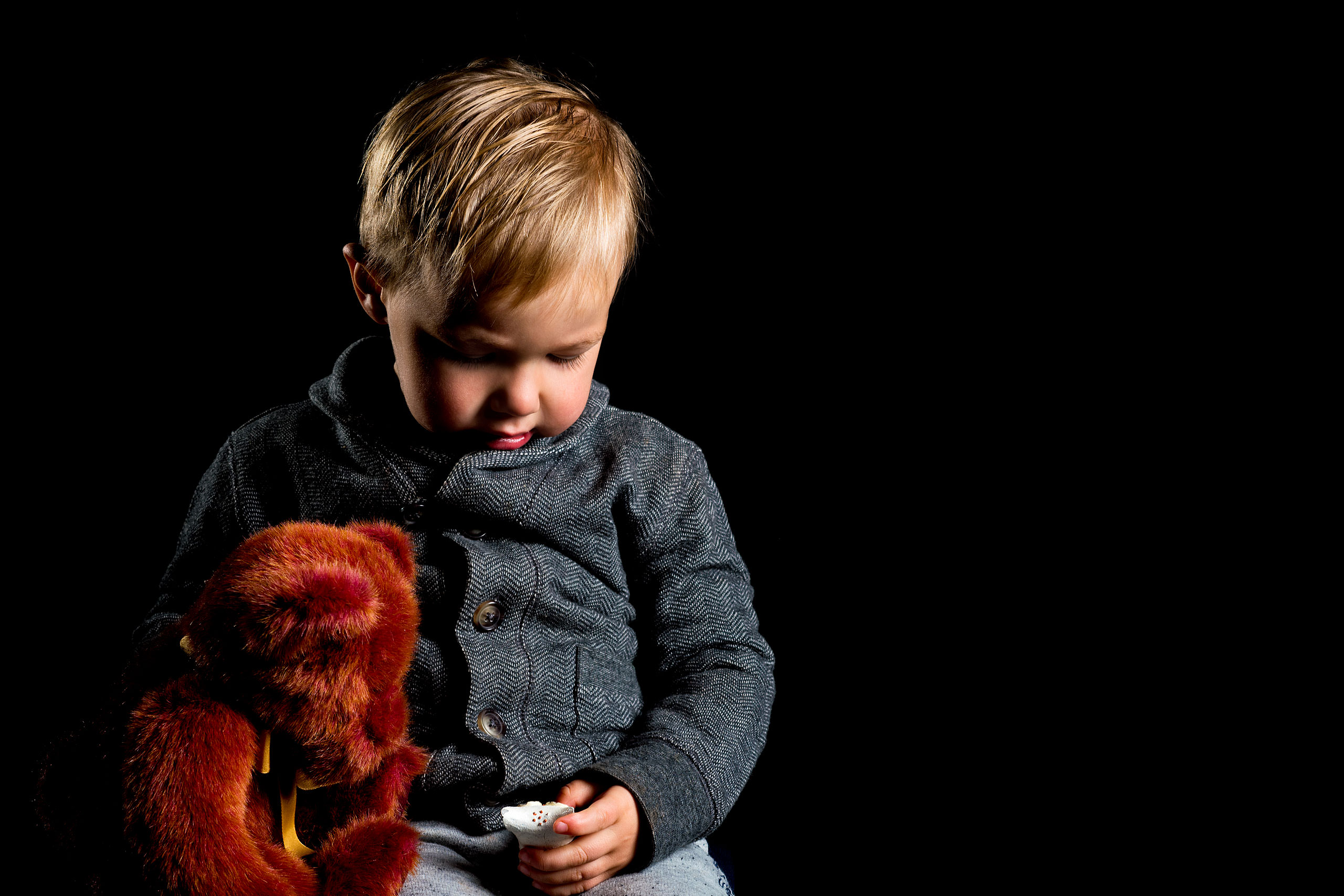a young boy holding a brown teddy bear looking at a toy for a calgary portrait studio session by sean leblanc