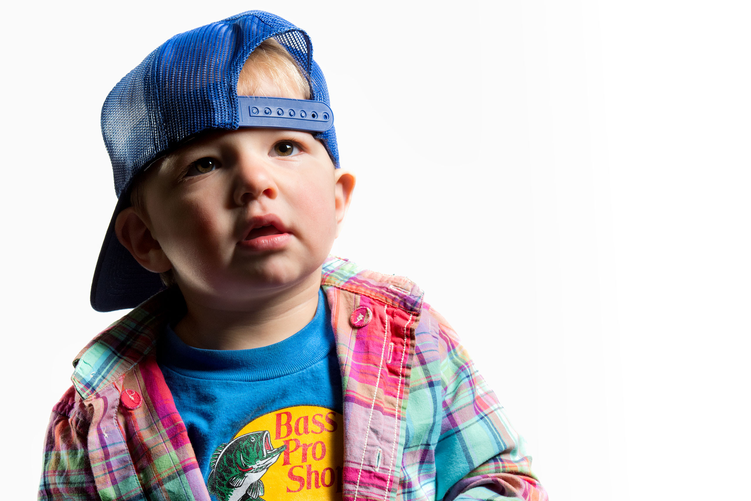 a young boy wearing a backwards blue hat looking up for a calgary portrait studio session by sean leblanc