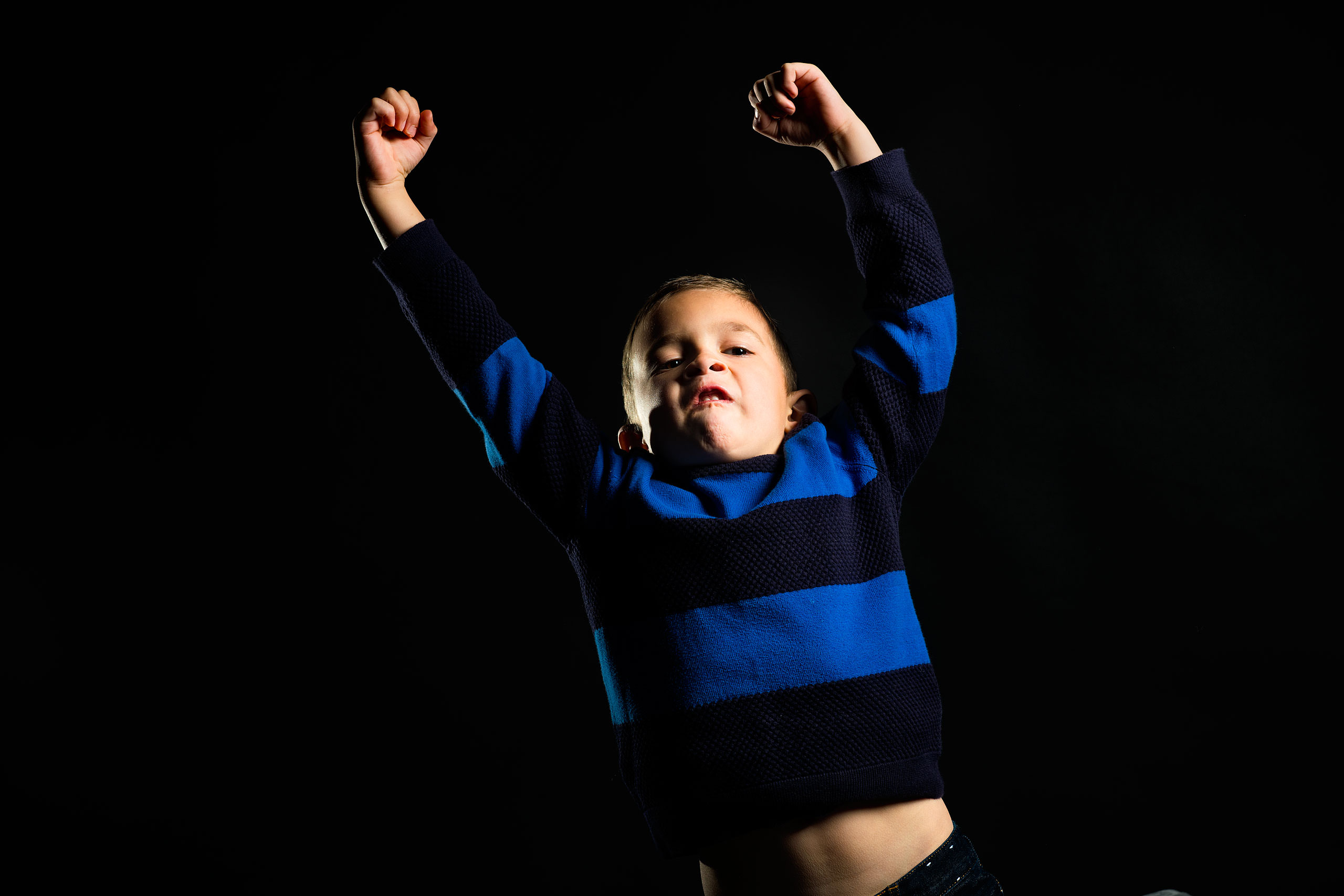 a young boy wearing a blue sweater pumping his arms for a calgary portrait studio session by sean leblanc