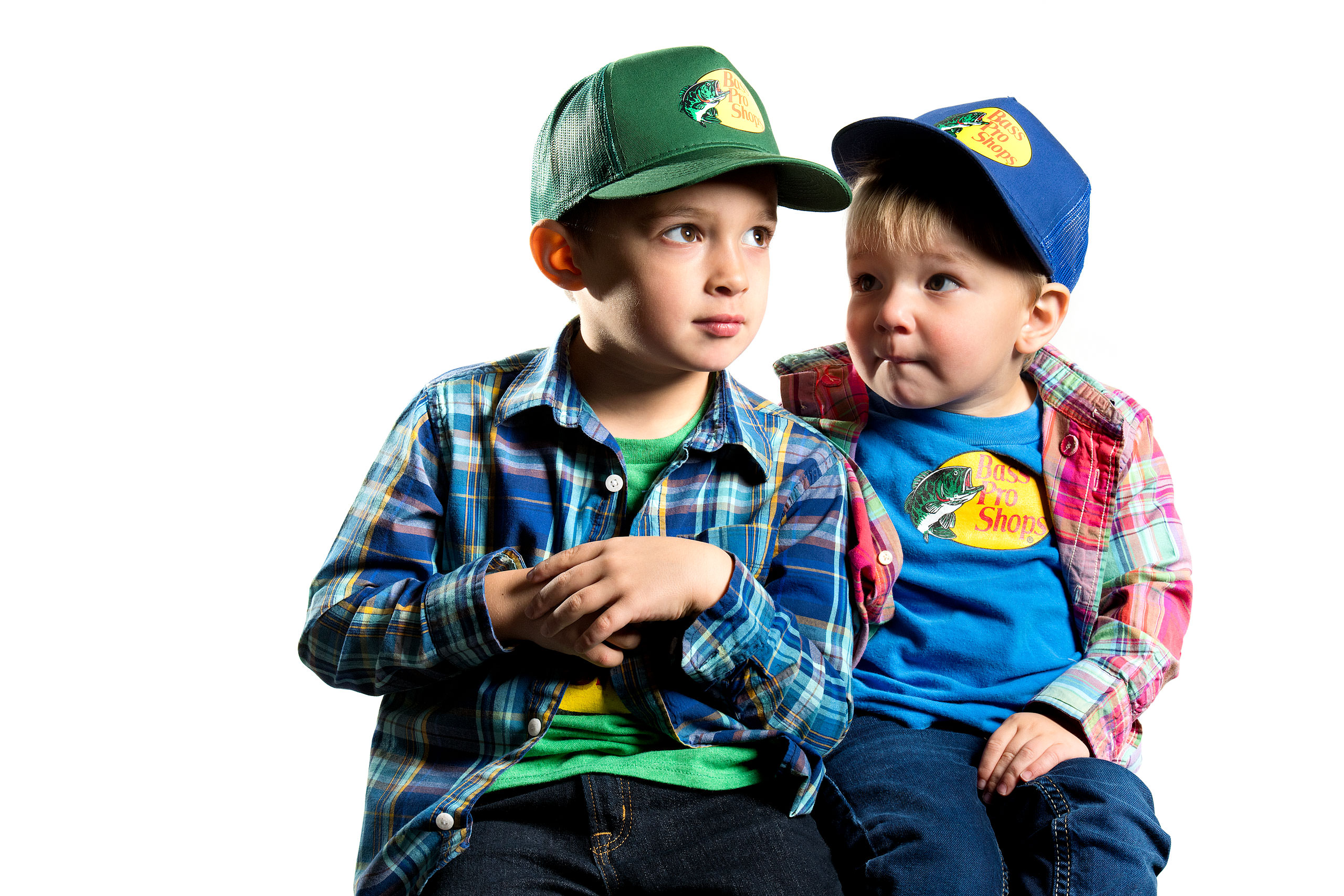 two young boys wearing hats and plaid shirts looking at each other by top family portrait photographer sean leblanc