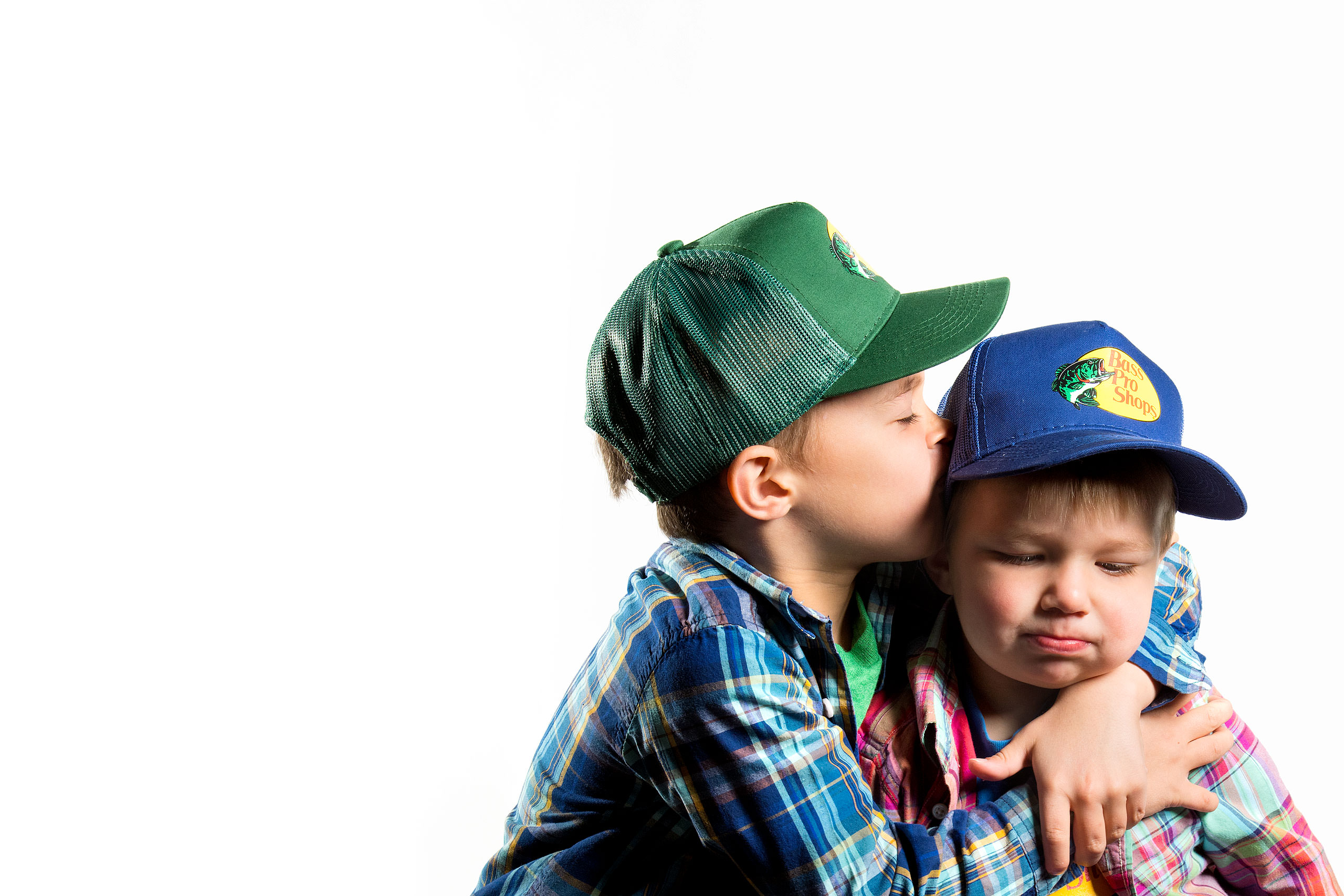 two brothers hugging each other and wearing hats for a calgary portrait studio session by sean leblanc