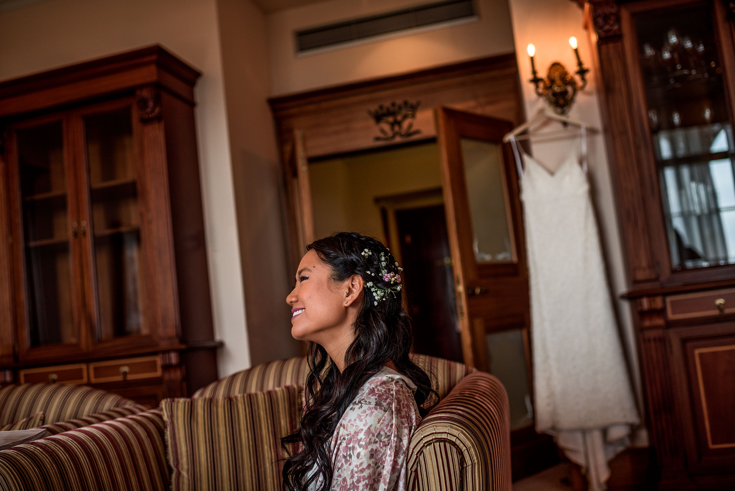 bride sitting on a sofa smiling with her wedding dress hanging in the background at castillo hotel son vida destination wedding by sean leblanc