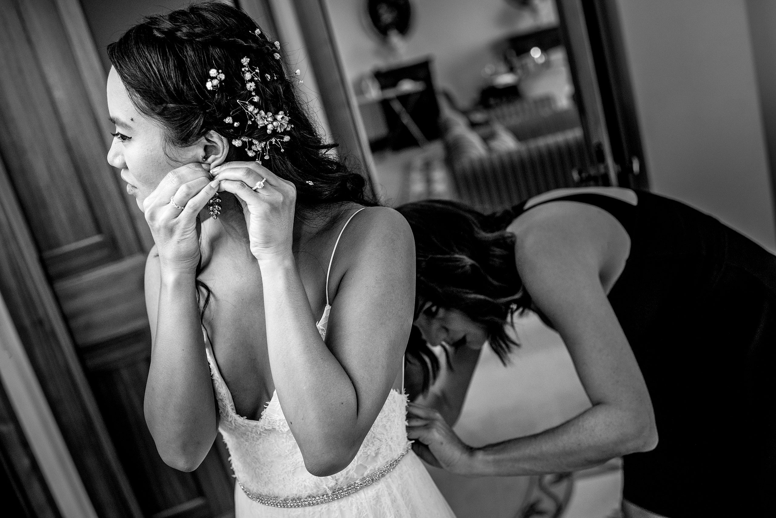 bridesmaid helping a bride with her dress at castillo hotel son vida destination wedding by sean leblanc