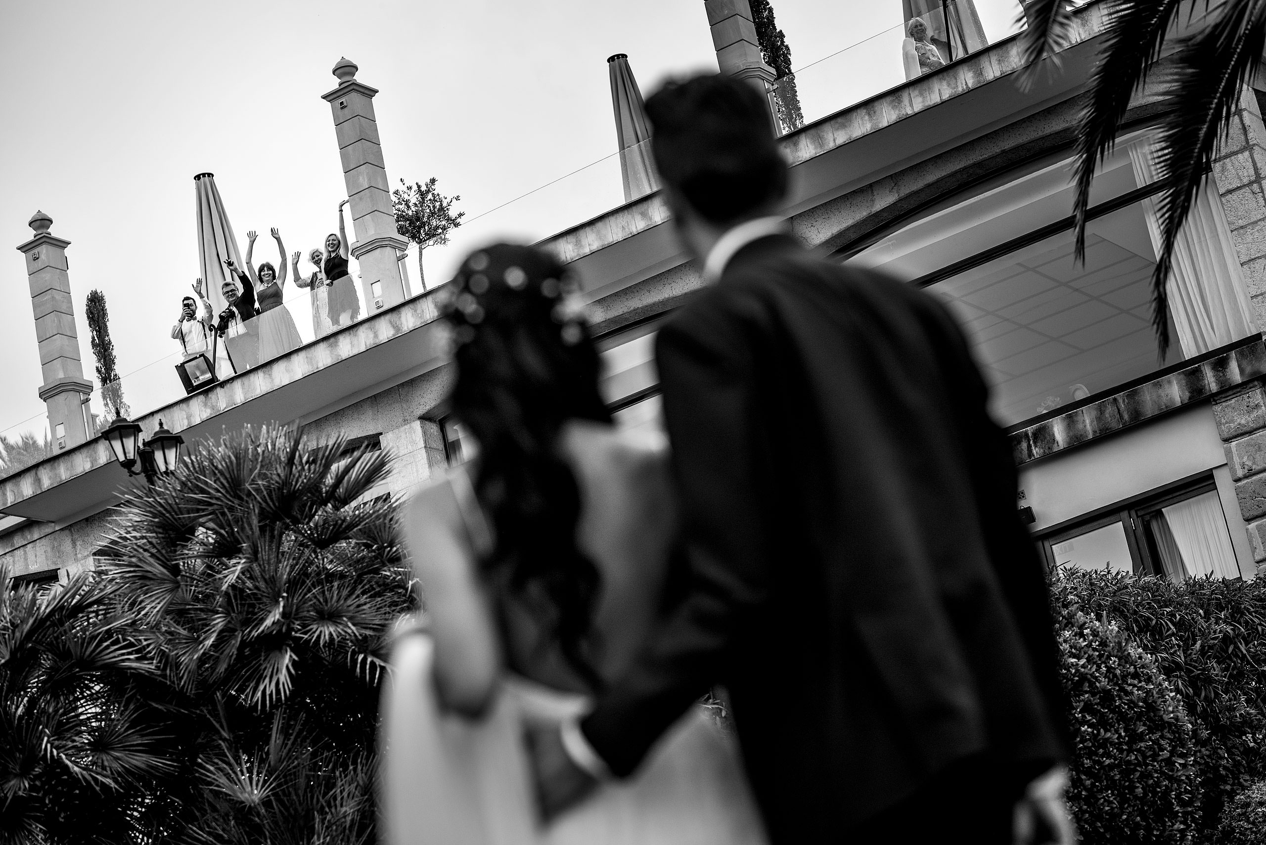 a bride and groom waving a friends on top of a roof at castillo hotel son vida destination wedding by sean leblanc