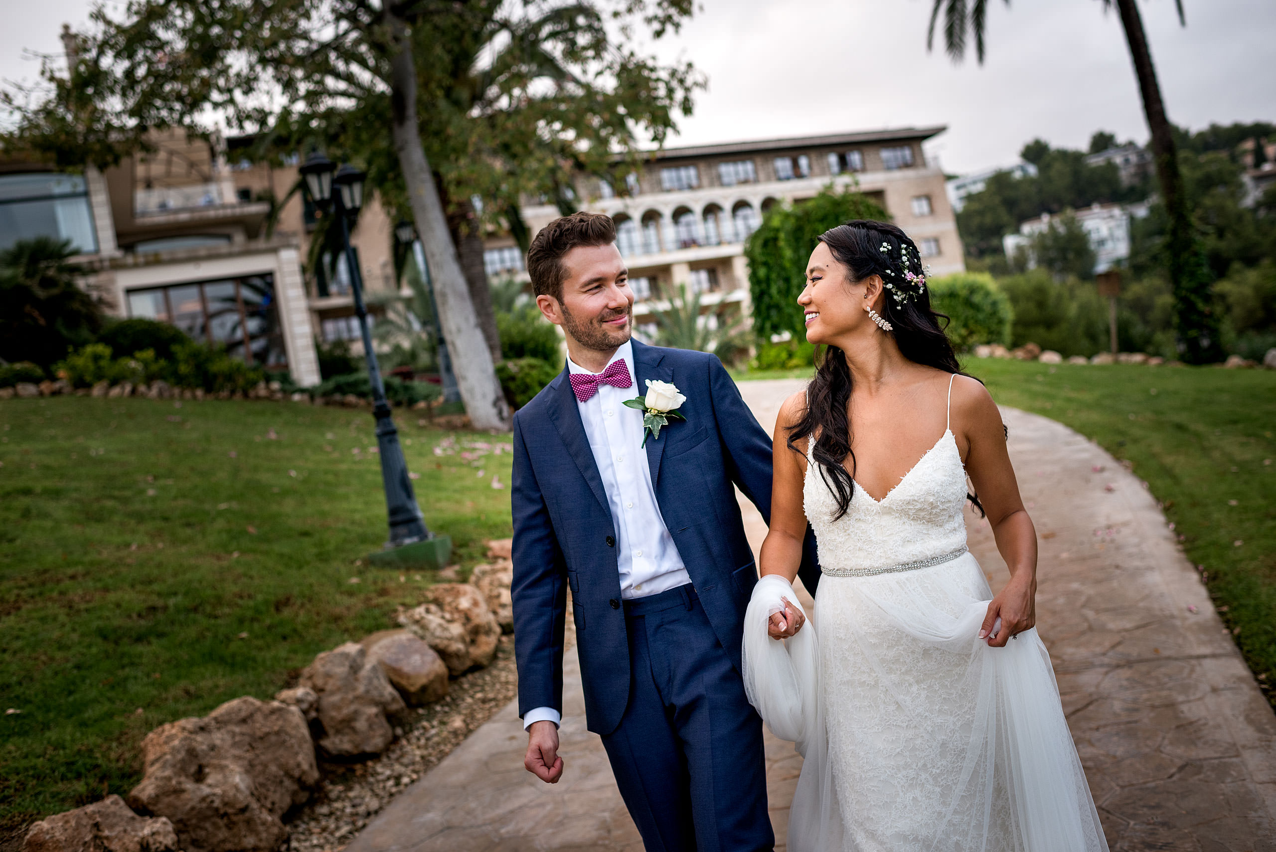 a bride and groom walking down a pathway with hotel in the background at castillo hotel son vida destination wedding by sean leblanc