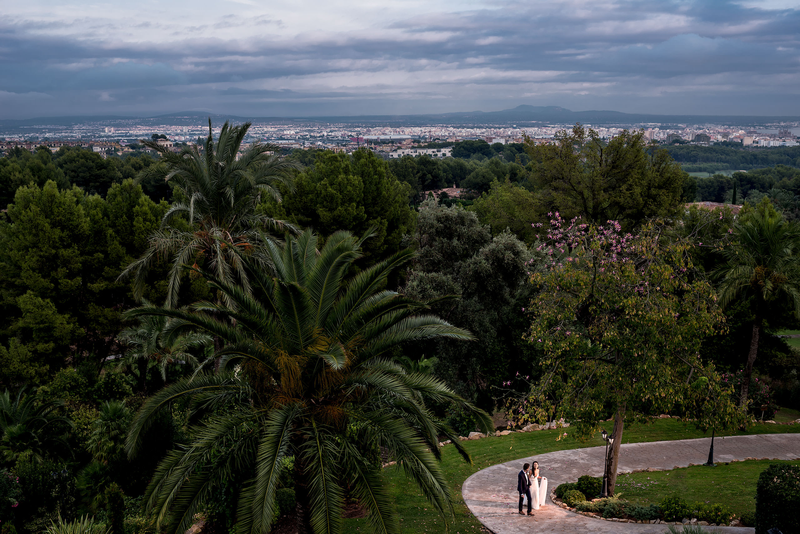 a bride and groom walking up a pathway with a town in the background at castillo hotel son vida destination wedding by sean leblanc