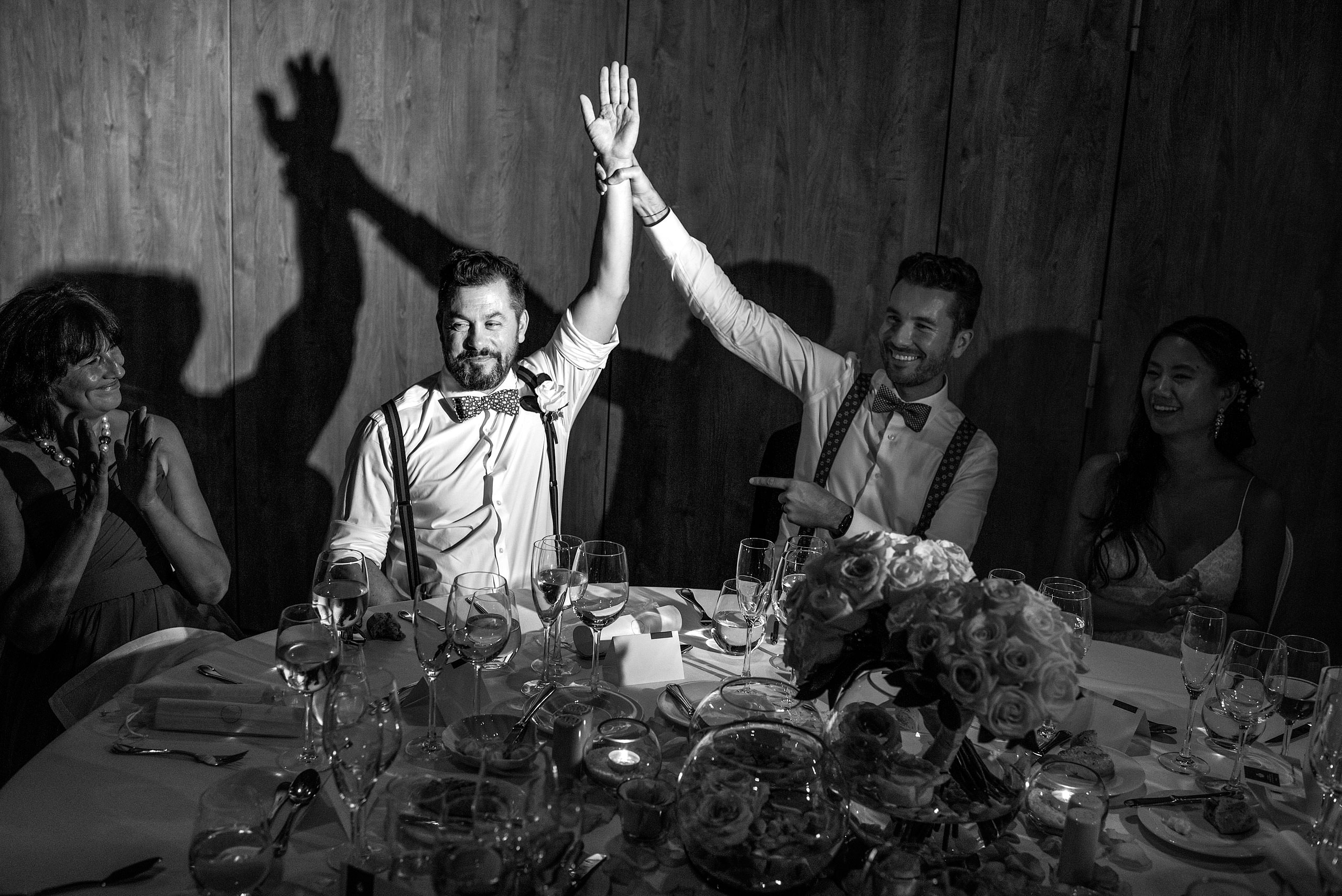 a groom holding up his groomsmen arm at the reception at castillo hotel son vida destination wedding by sean leblanc