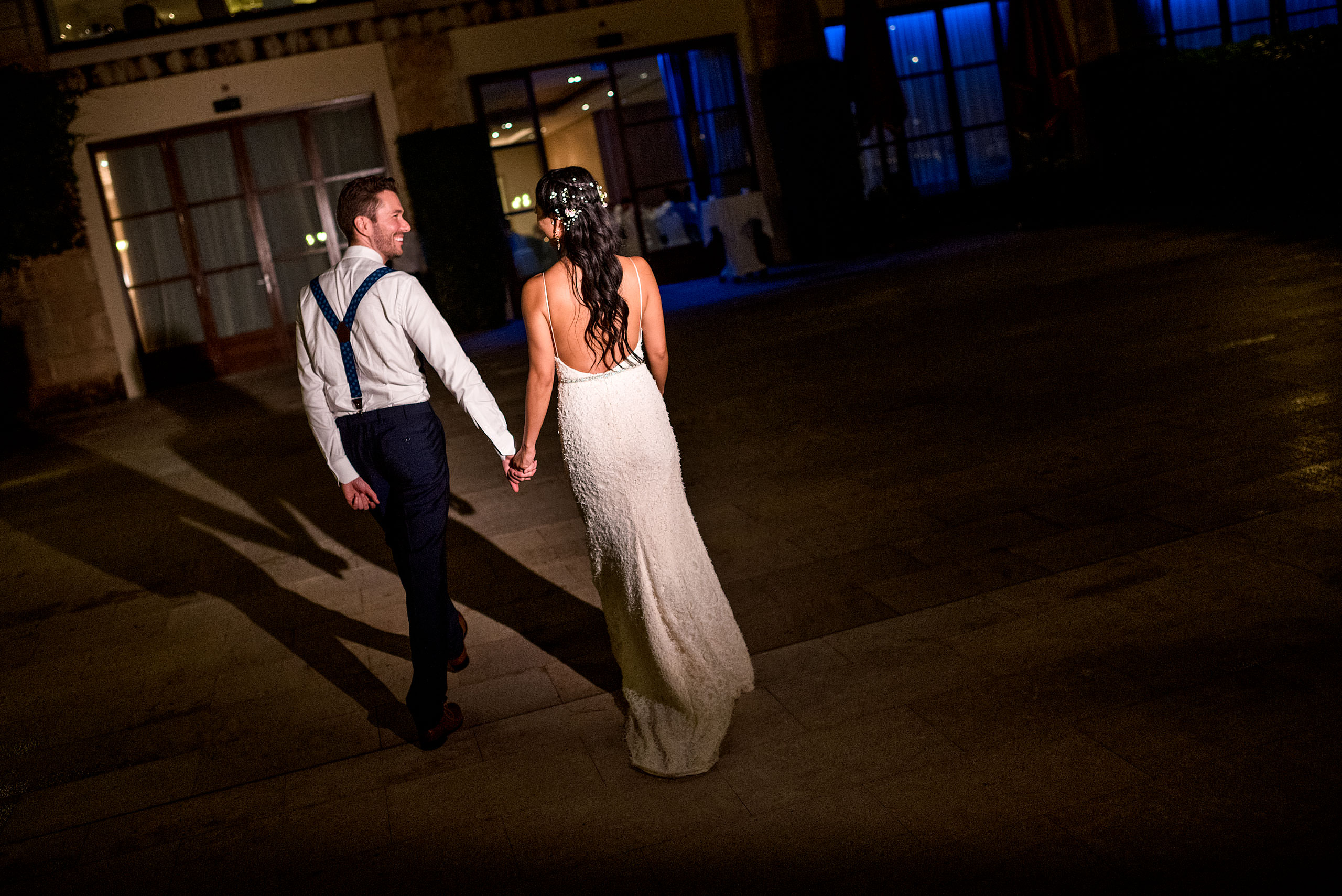 a bride and groom walking towards a building together at castillo hotel son vida destination wedding by sean leblanc