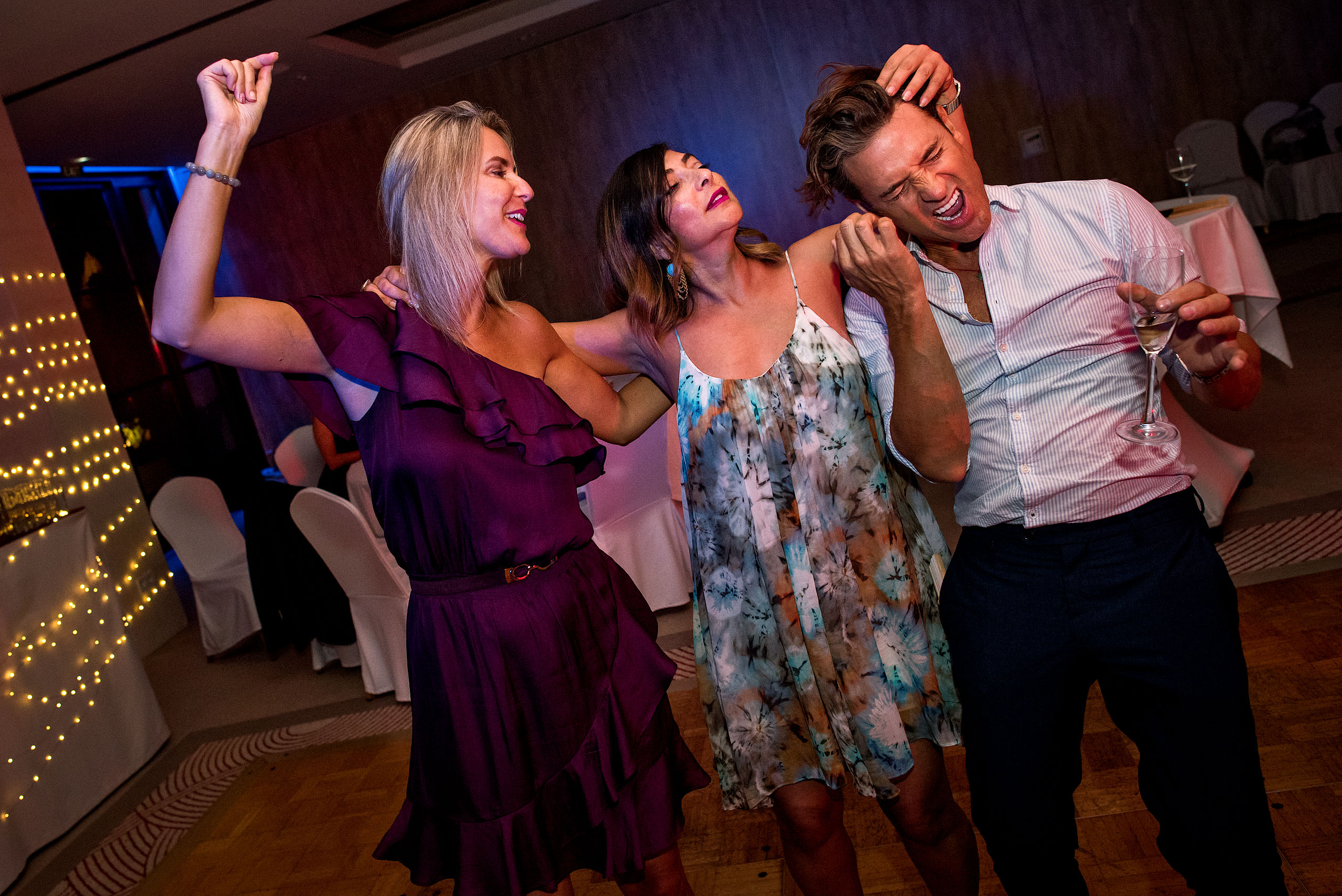 two women and one man dancing together at castillo hotel son vida destination wedding by sean leblanc