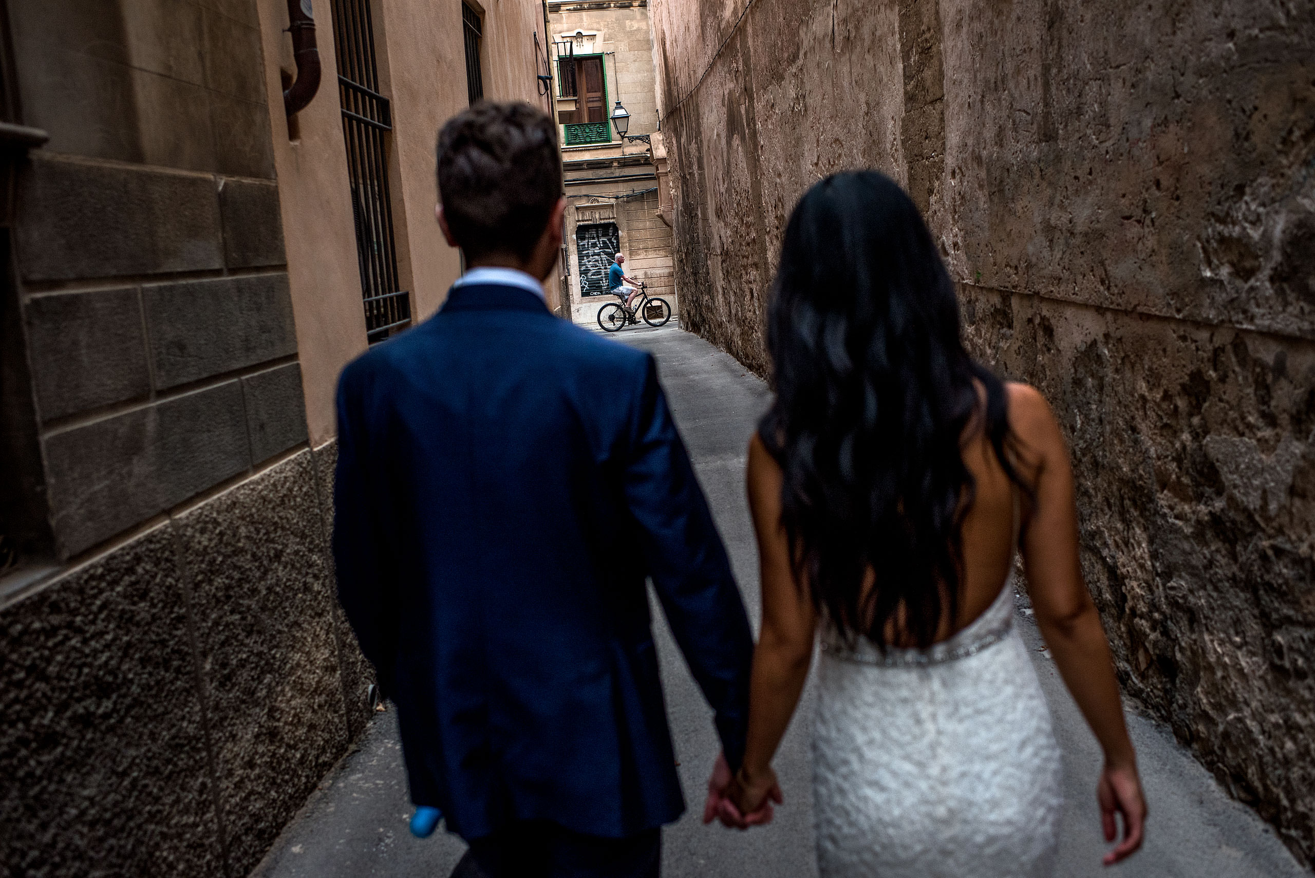 a bride and groom walking down an alleyway at castillo hotel son vida destination wedding by sean leblanc