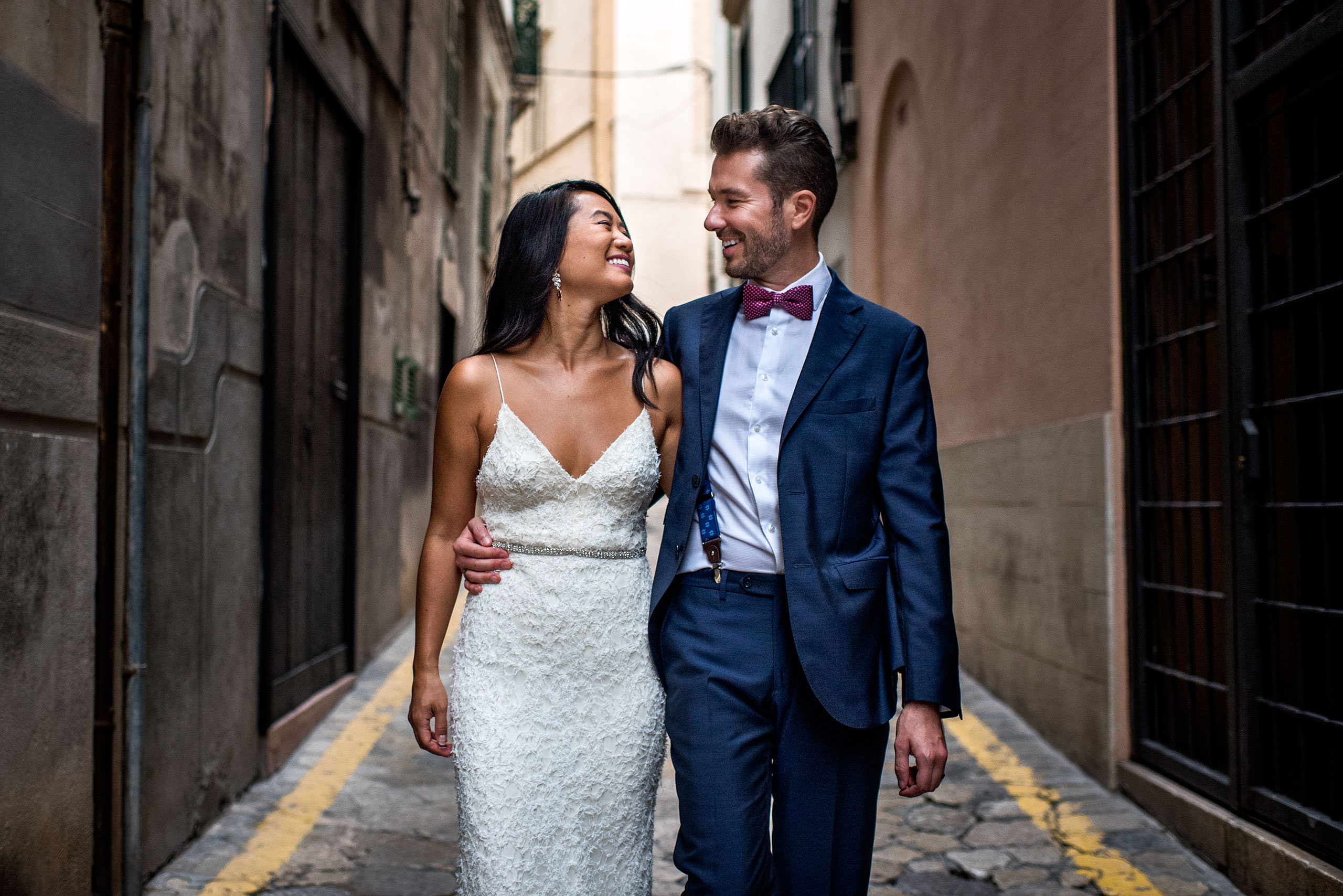 a bride and groom walking down an alleyway with their arms around each other at castillo hotel son vida destination wedding by sean leblanc