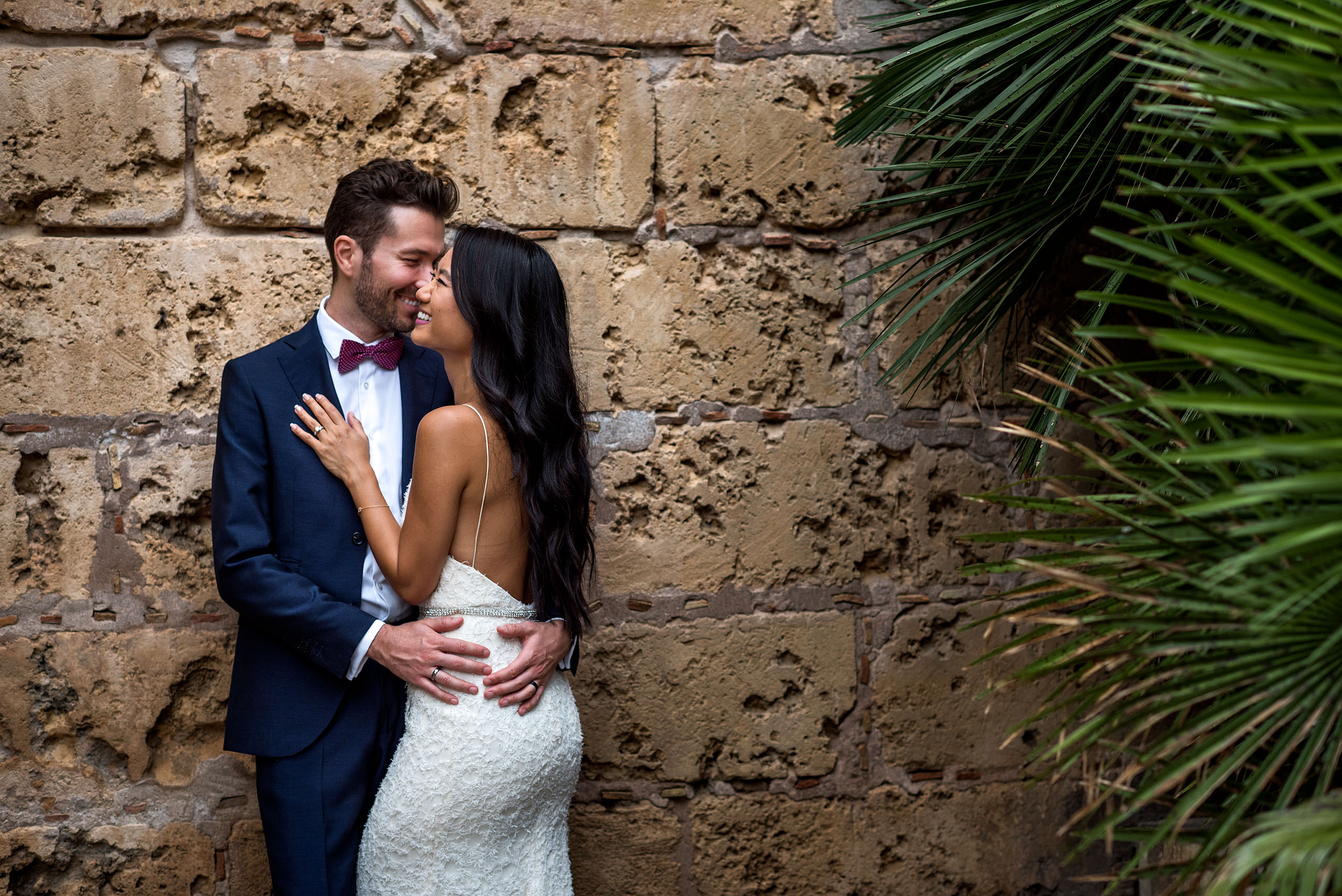 a bride and groom embracing in front of a brick wall at castillo hotel son vida destination wedding by sean leblanc