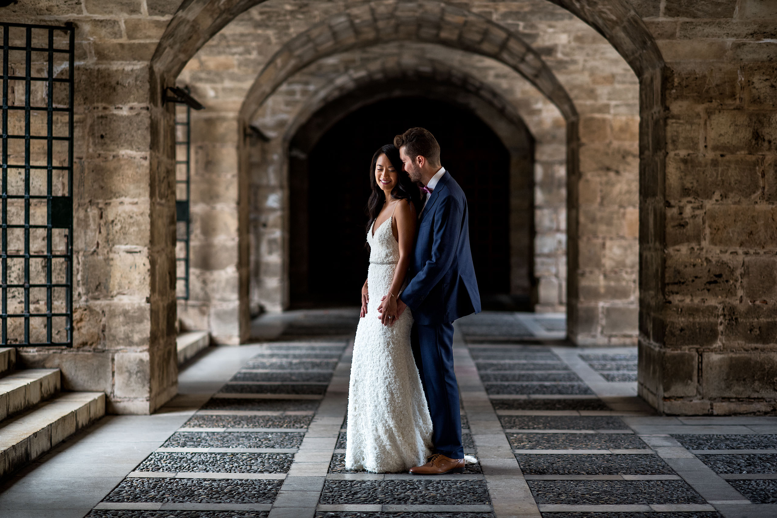 groom embracing his bride at an old castle at castillo hotel son vida destination wedding by sean leblanc