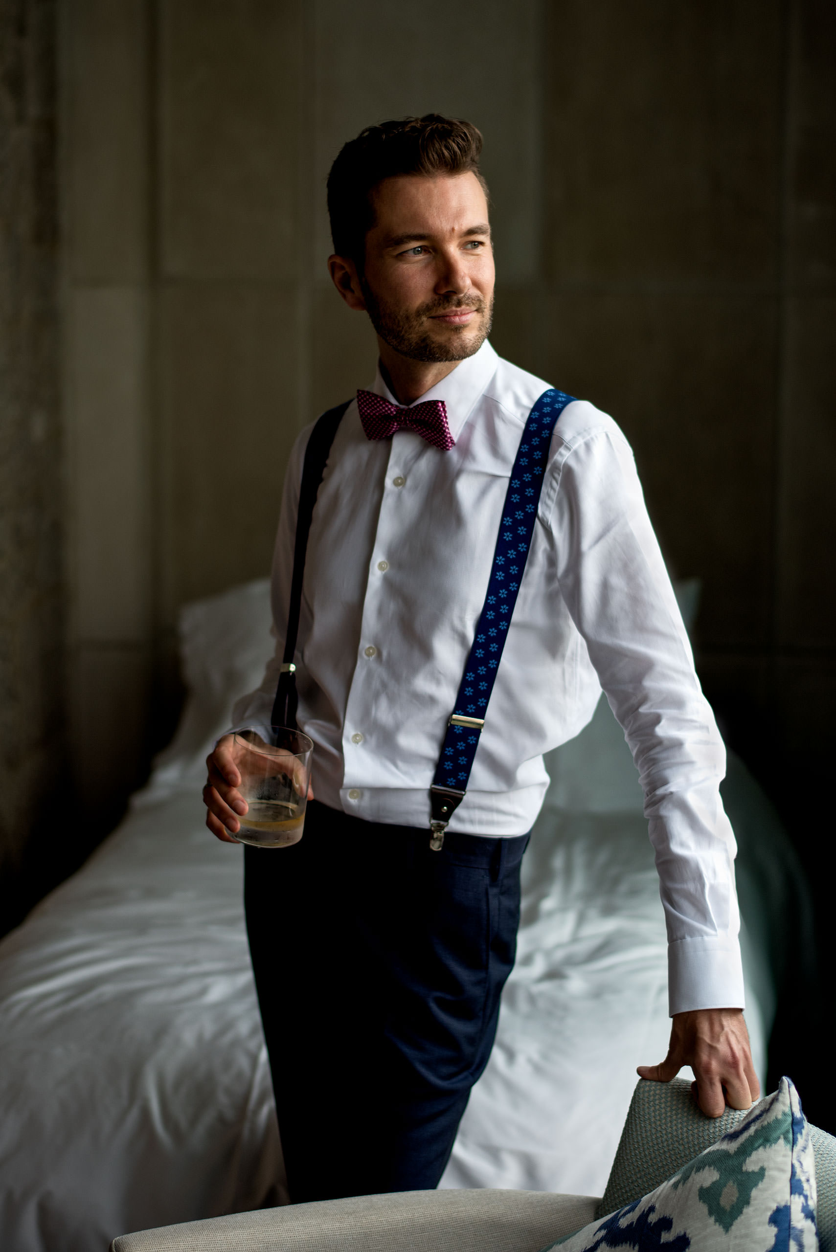 groom leaning against a chair holding a drink at castillo hotel son vida destination wedding by sean leblanc