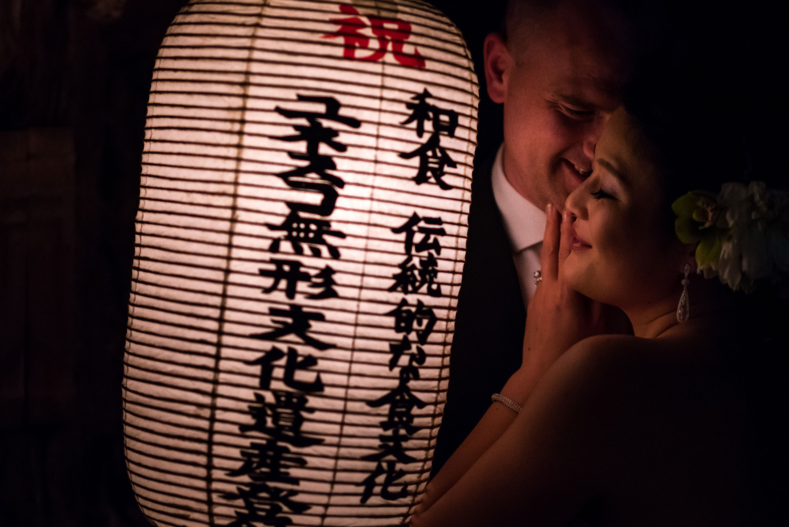 bride and groom hugging by a Japanese lantern by Japan Destination Wedding Photographer Sean LeBlanc