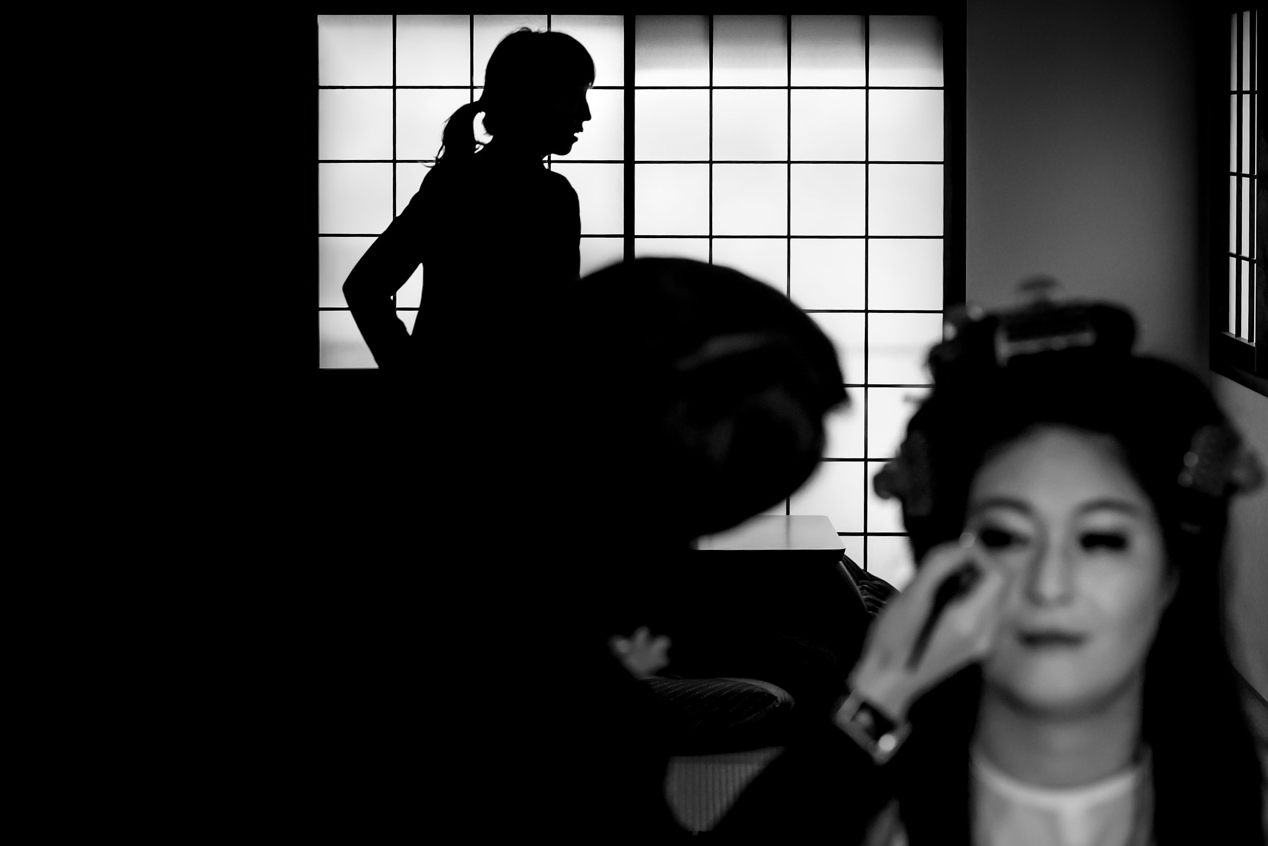 a Japanese women getting her makeup done with a girl in the background by Japan Destination Wedding Photographer Sean LeBlanc