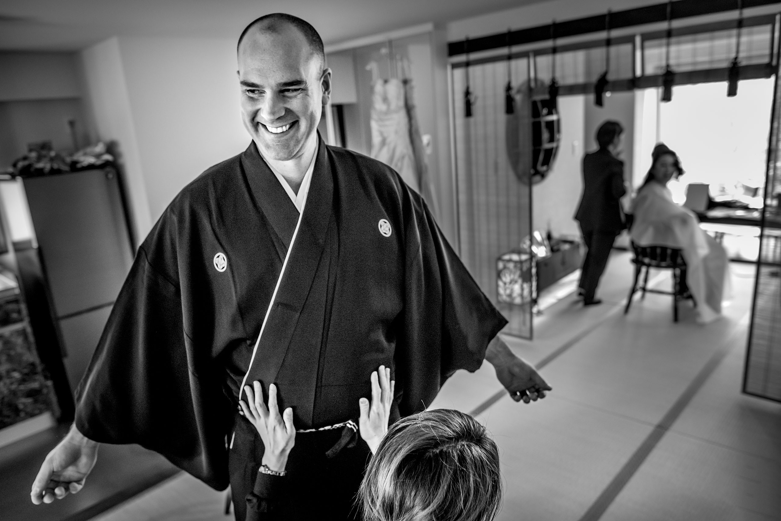 a groom getting help with his Japanese outfit by Japan Destination Wedding Photographer Sean LeBlanc