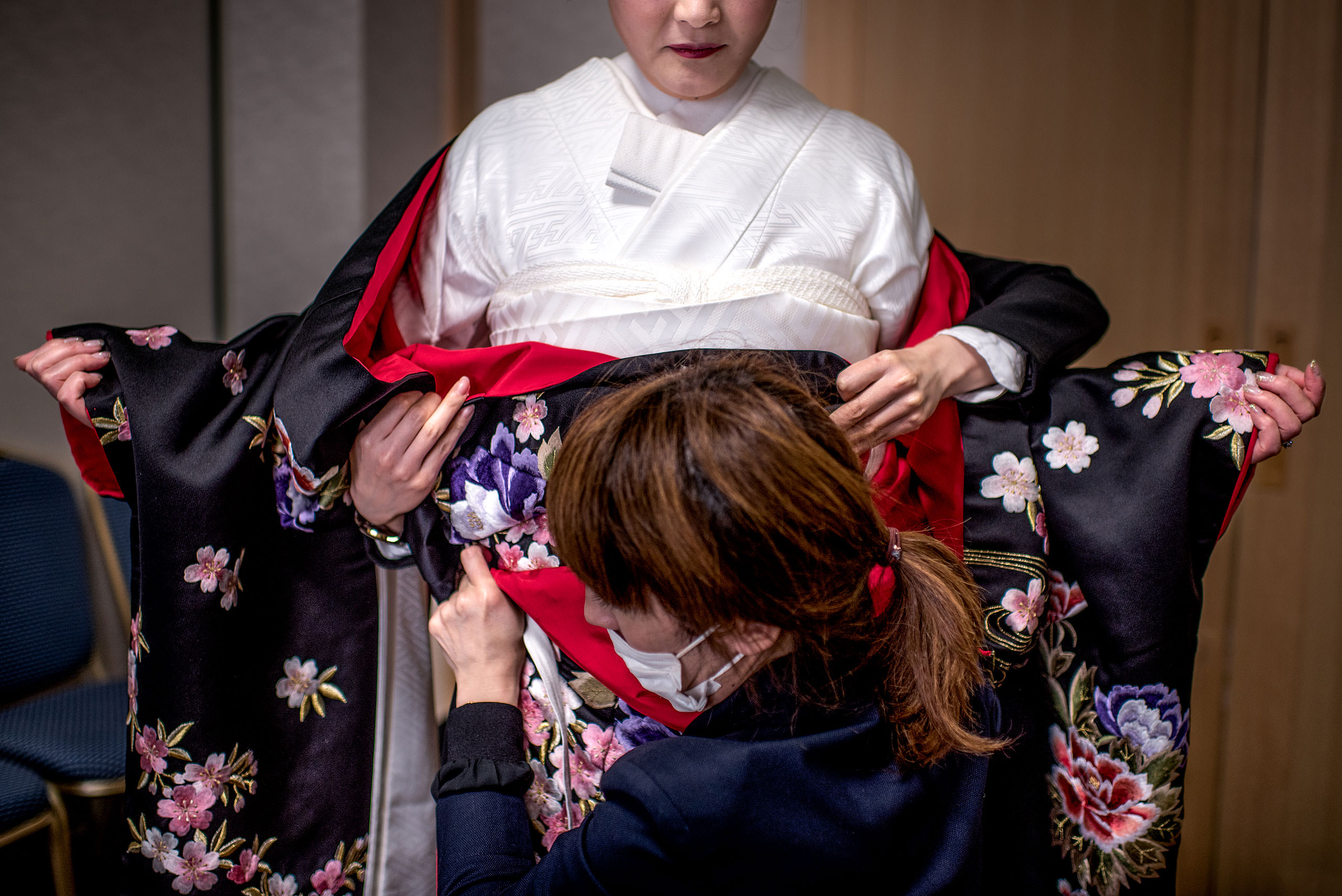 a Japanese women being helped with her kimono by Japan Destination Wedding Photographer Sean LeBlanc