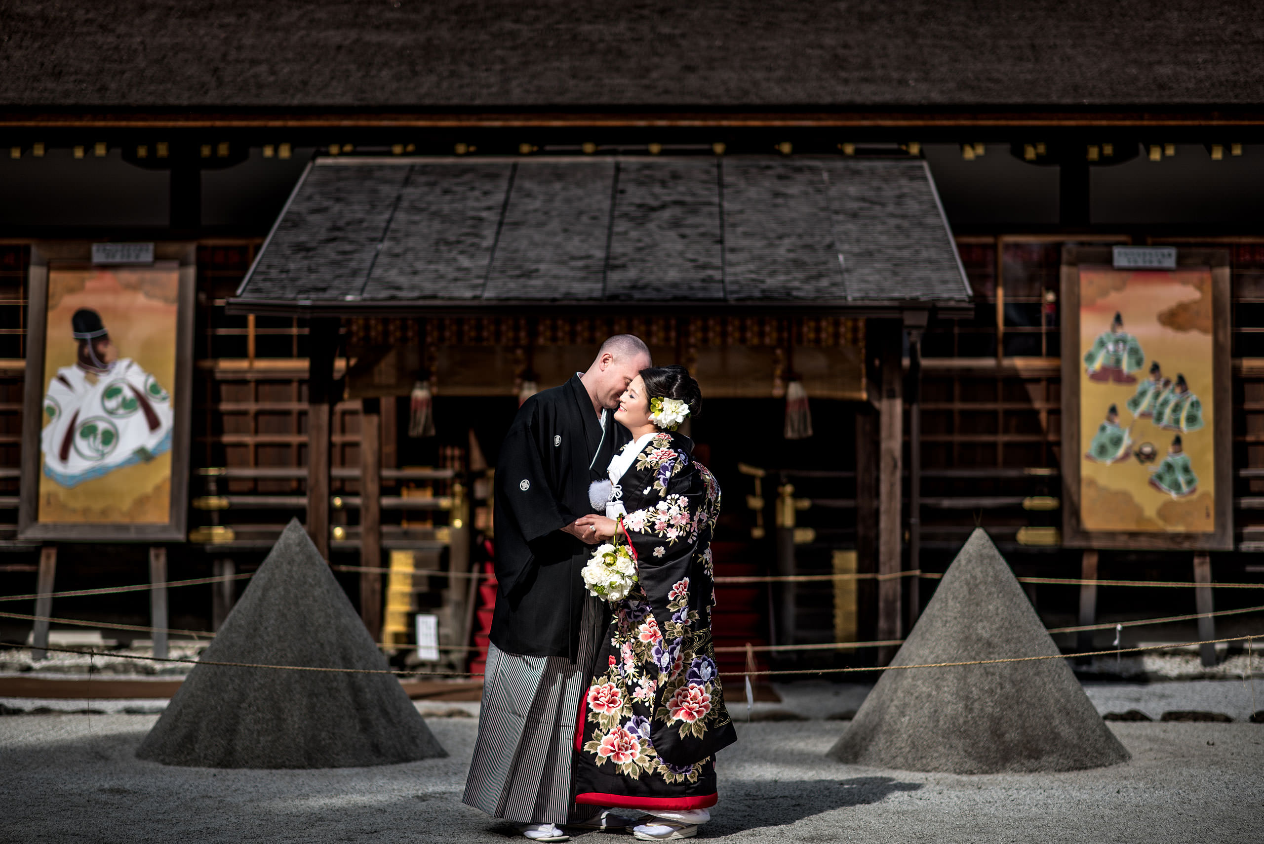 Japanese bride and groom embracing in front of a Japanese temple