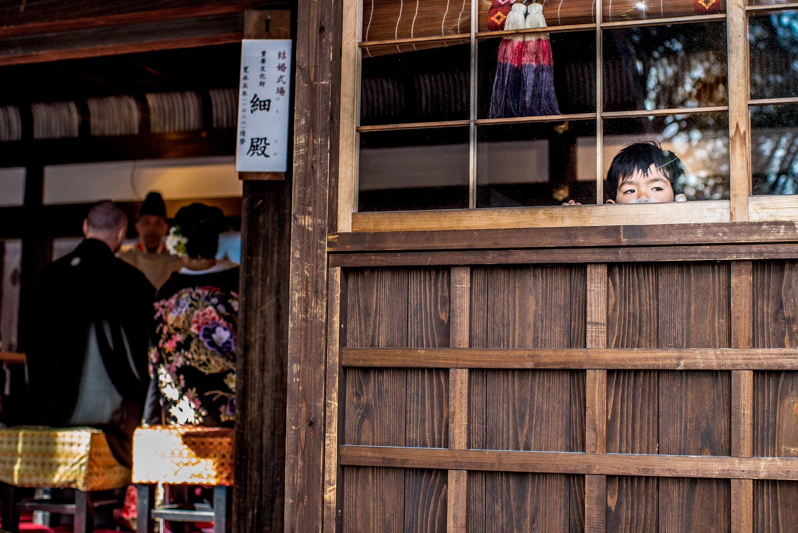 a boy looking out a widow at a ceremony by Japan Destination Wedding Photographer Sean LeBlanc