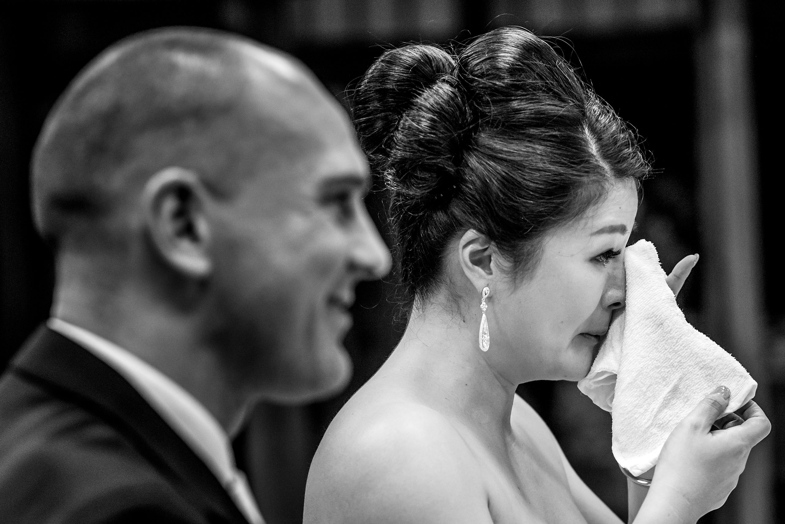 an emotional bride wiping a tear from her face by Japan Destination Wedding Photographer Sean LeBlanc