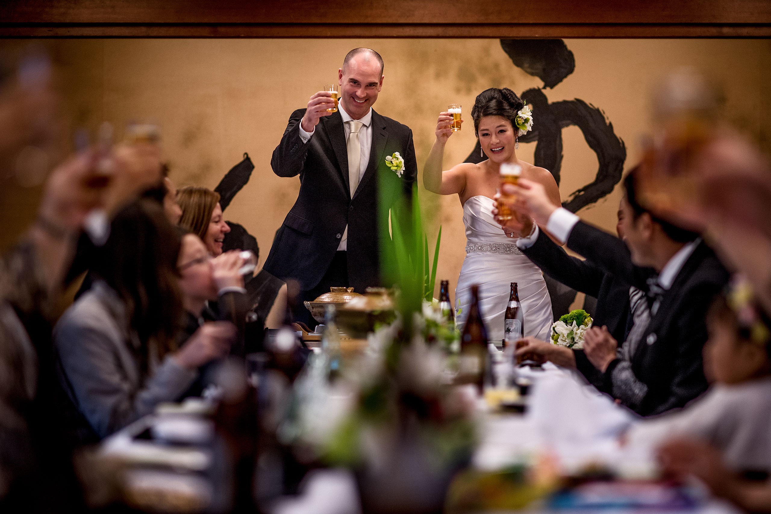 a bride and groom raising their glasses to their guests by Japan Destination Wedding Photographer Sean LeBlanc