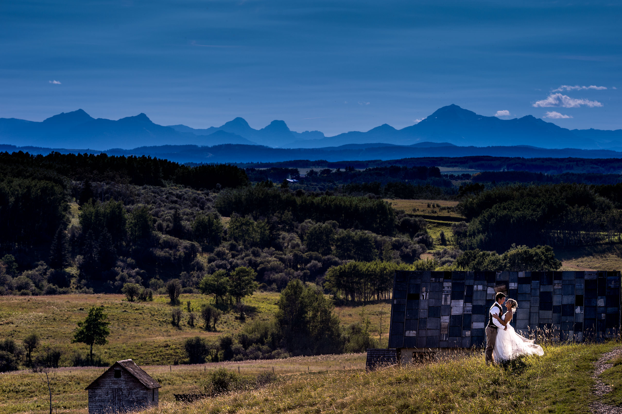 bride and groom posing with the mountains in the background by top calgary wedding photographer sean leblanc