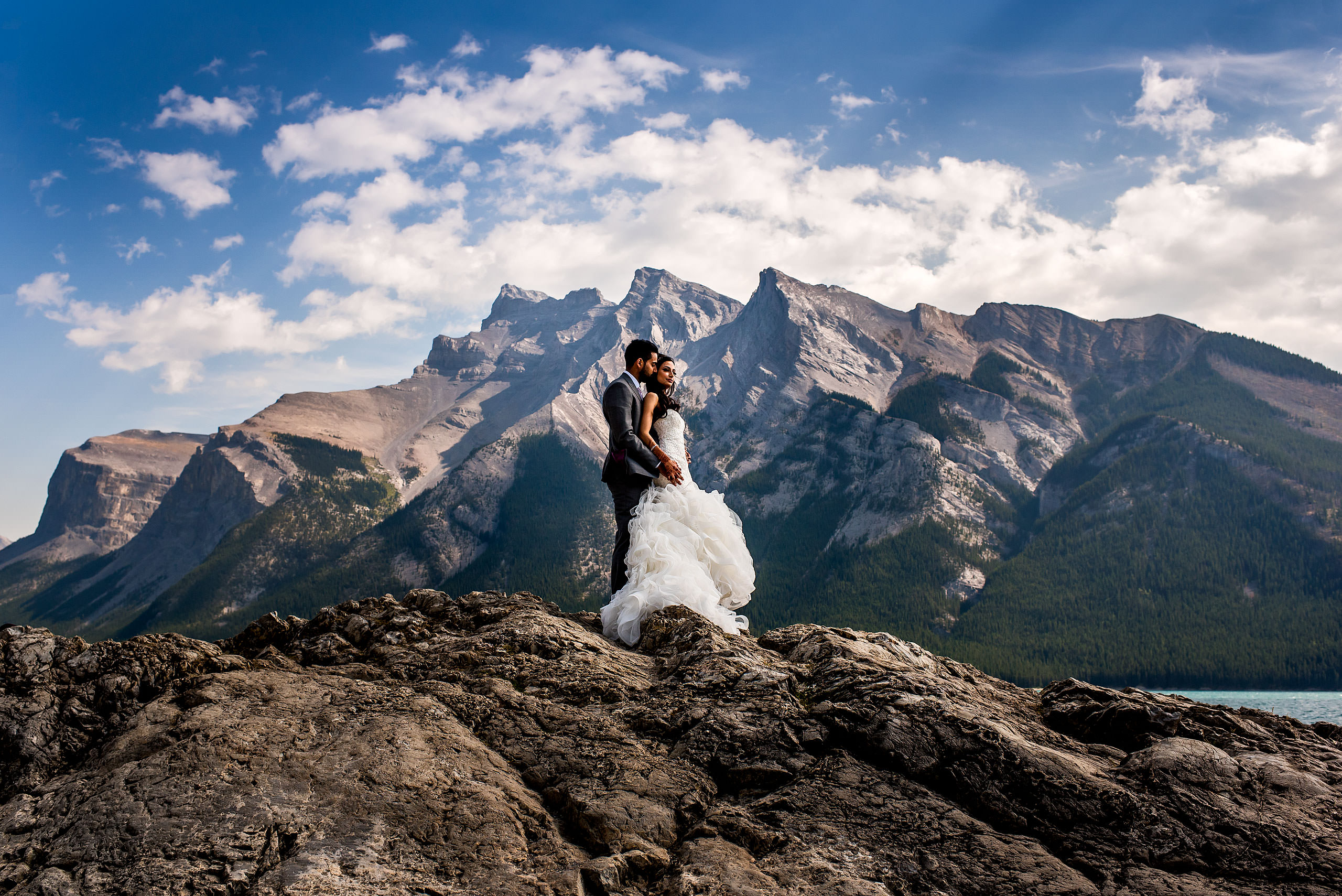 bride and groom posing on a rock by Banff wedding photographer