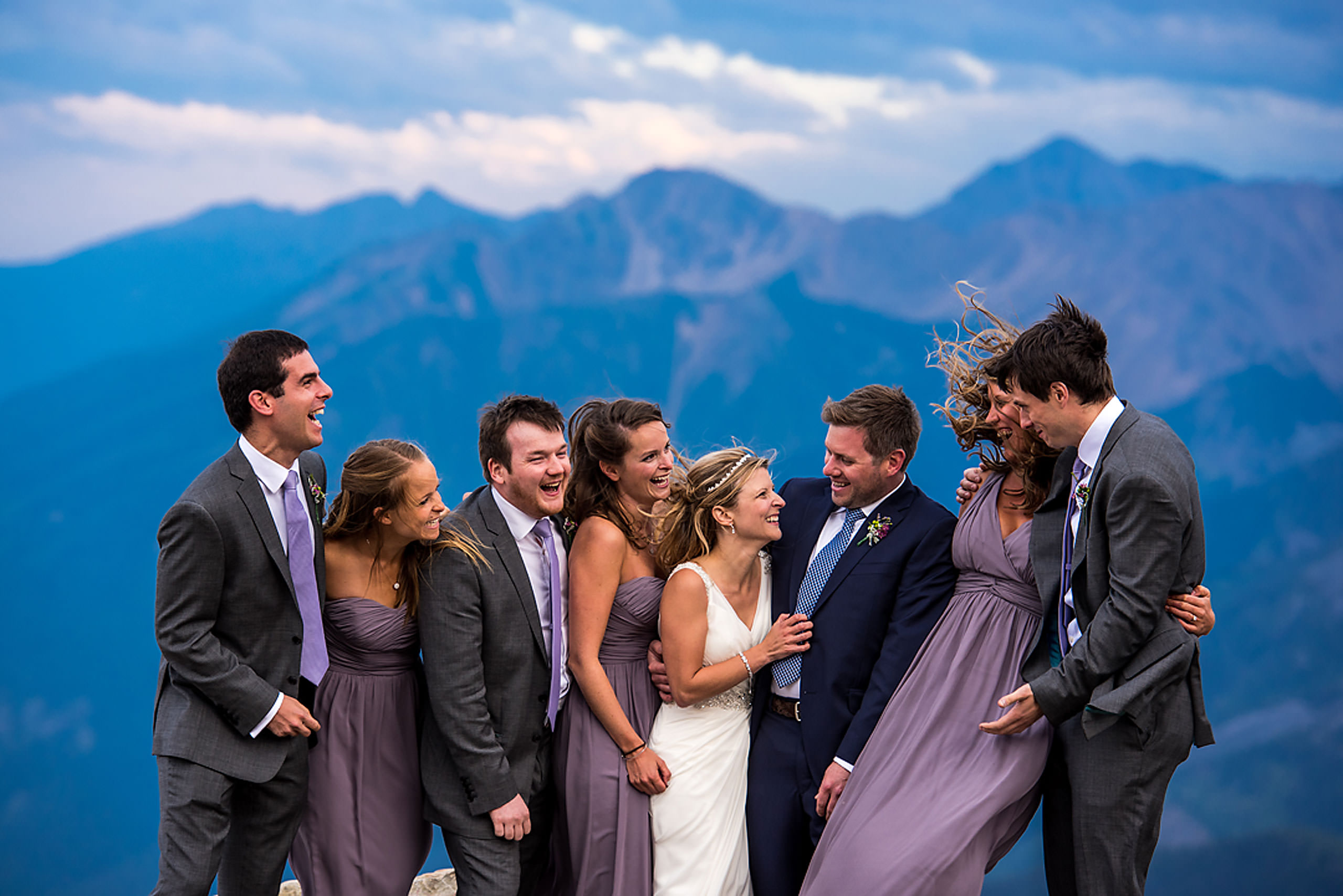 bridal party laughing at each other on the top of a mountain at summer kicking horse wedding