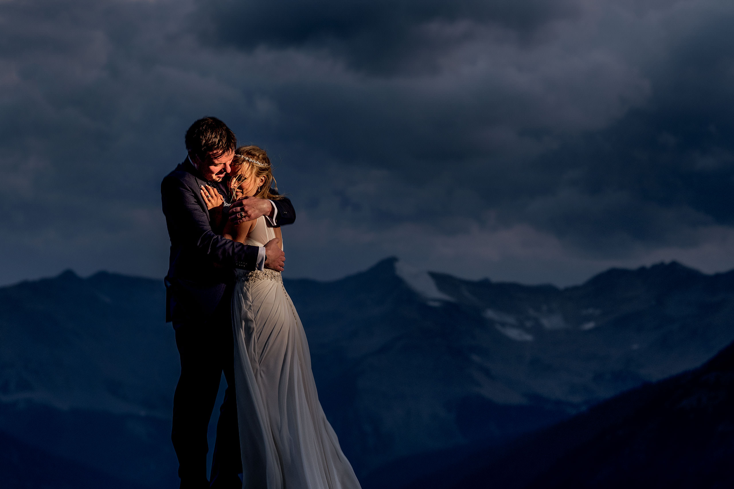 bride and groom embracing on top of a mountain at dusk at summer kicking horse wedding