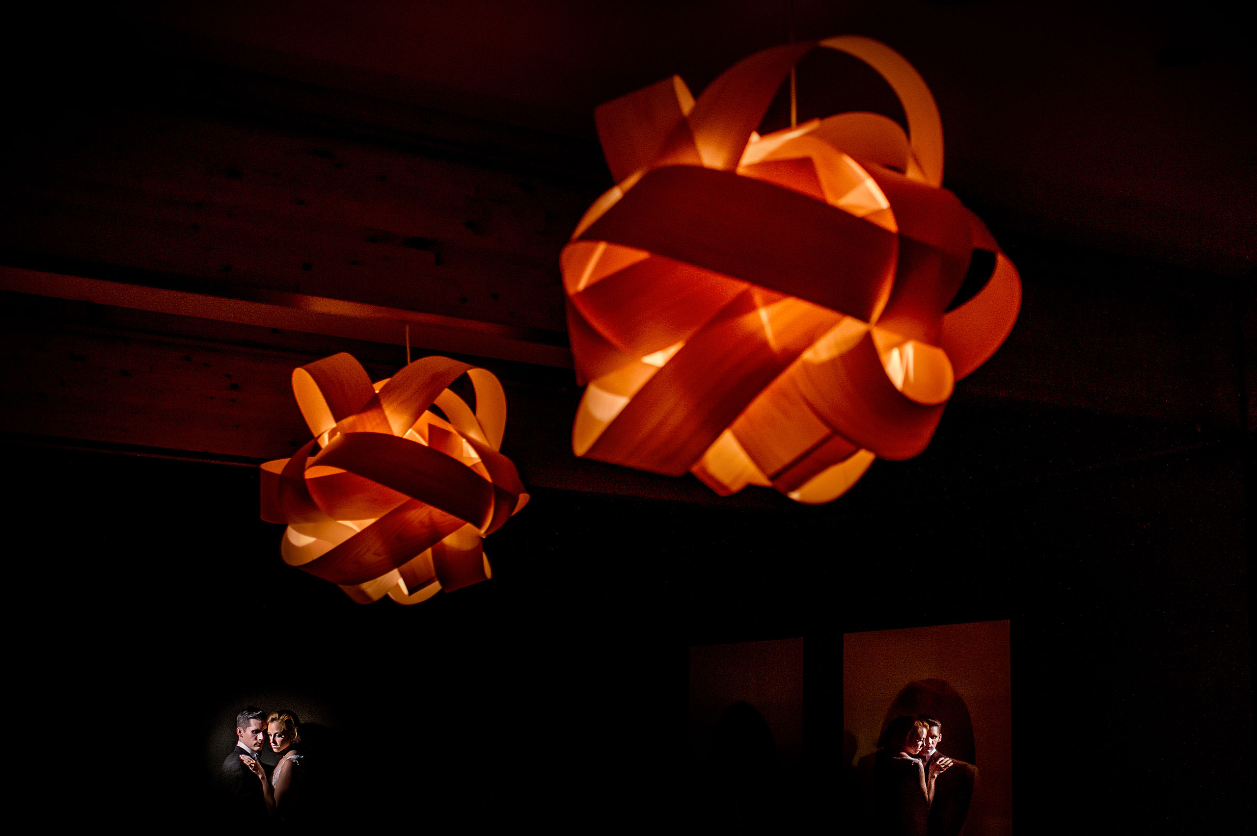 bride and groom embracing next to a wall with two large light fixtures in the foreground at Priddis Azuridge Wedding by sean leblanc