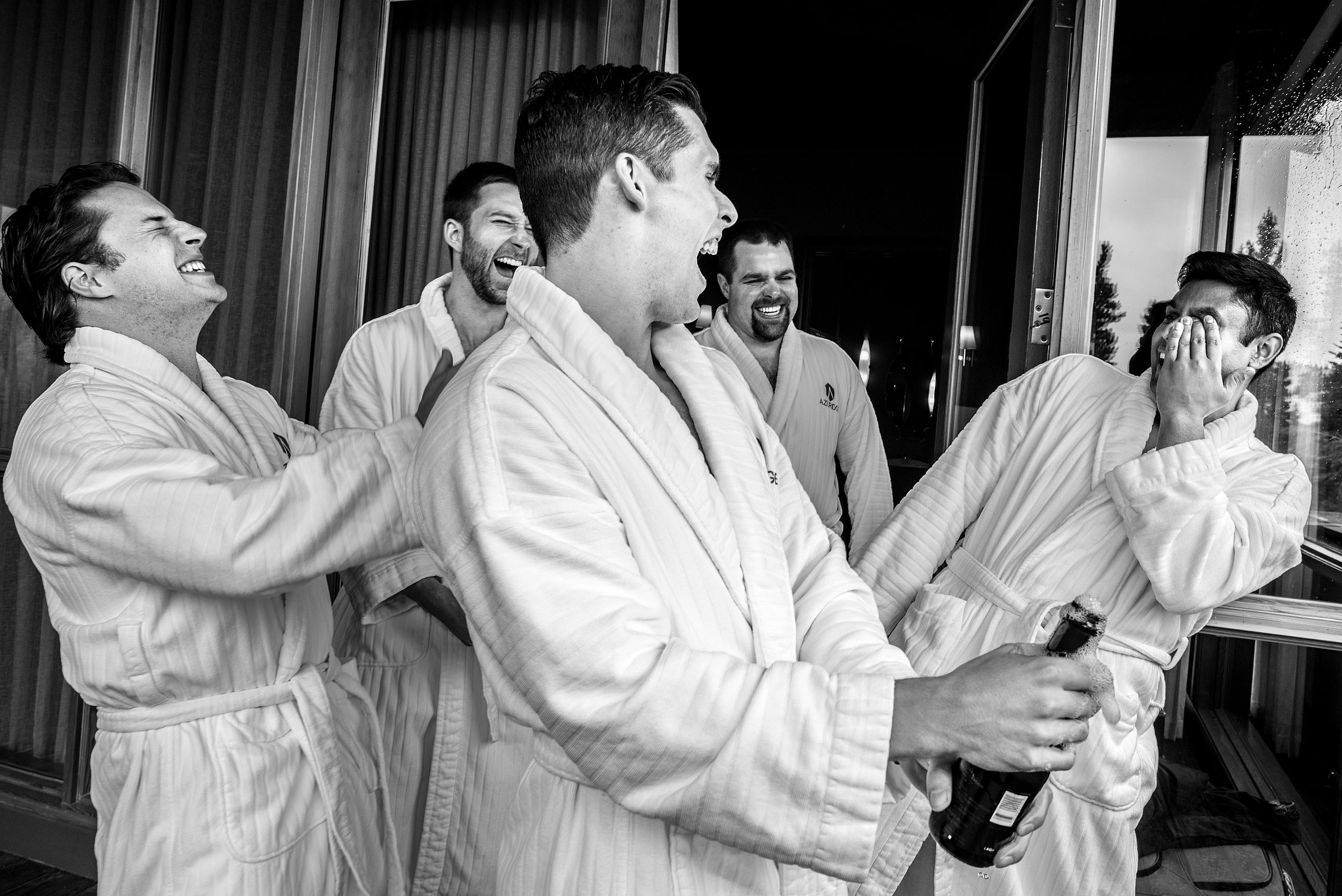 groomsmen laughing at each other in their bathrobe at Priddis Azuridge Wedding by sean leblanc