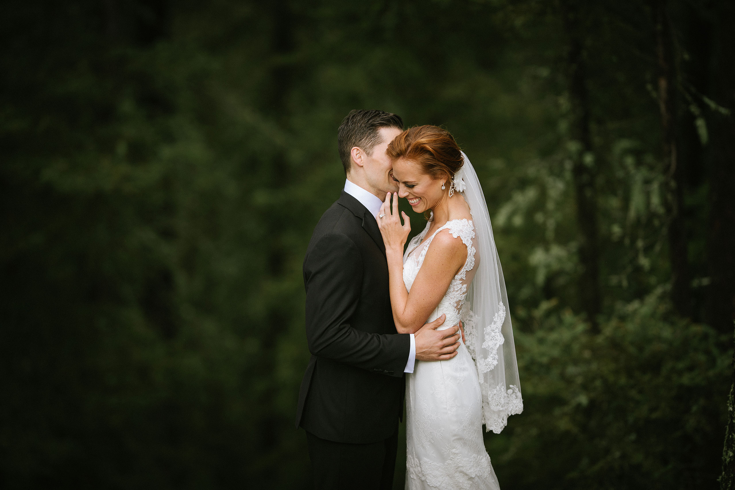 groom whispering into brides ear by top calgary wedding photographer sean leblanc
